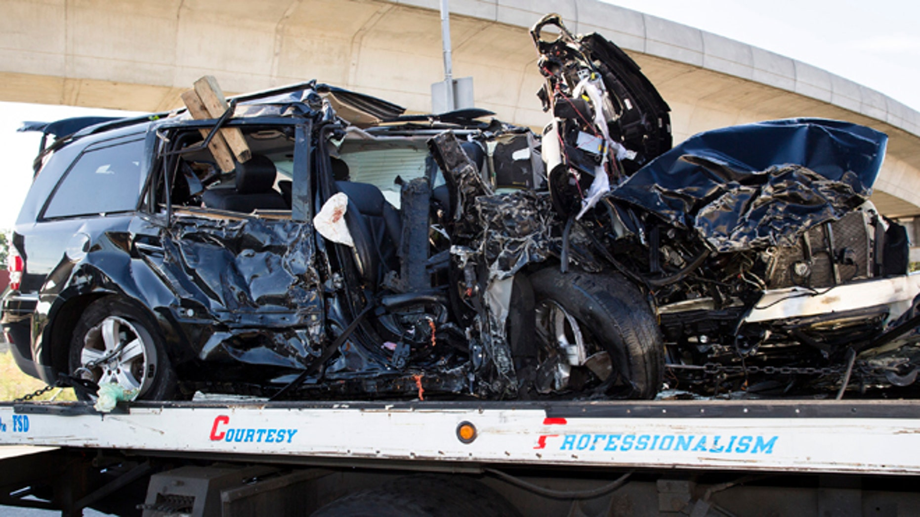 July 22, 2012: Authorities clear an automobile involved in a single-vehicle crash that took the lives of five people, including two children, near the Van Wyck Expressway in the Queens borough of New York.