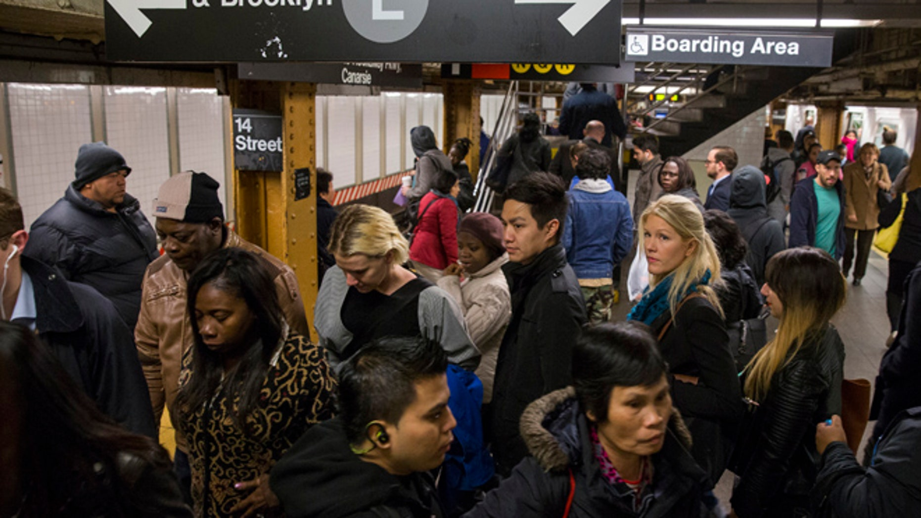 FILE Commuters depart an L train during the morning commute.
