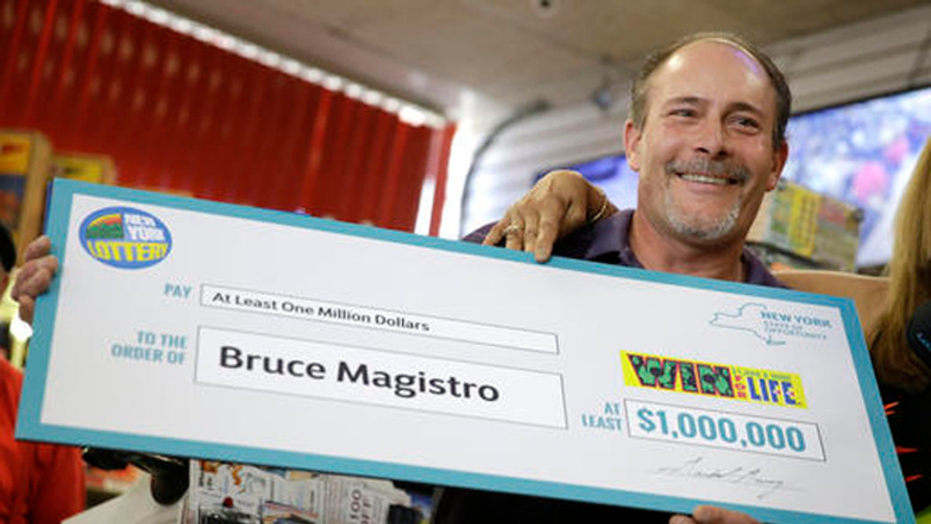 Bruce Magistro holds up a check while talking to reporters about winning $1 million in the New York Lottery for a second time during a news conference in Babylon, N.Y., Wednesday, May 11, 2016.