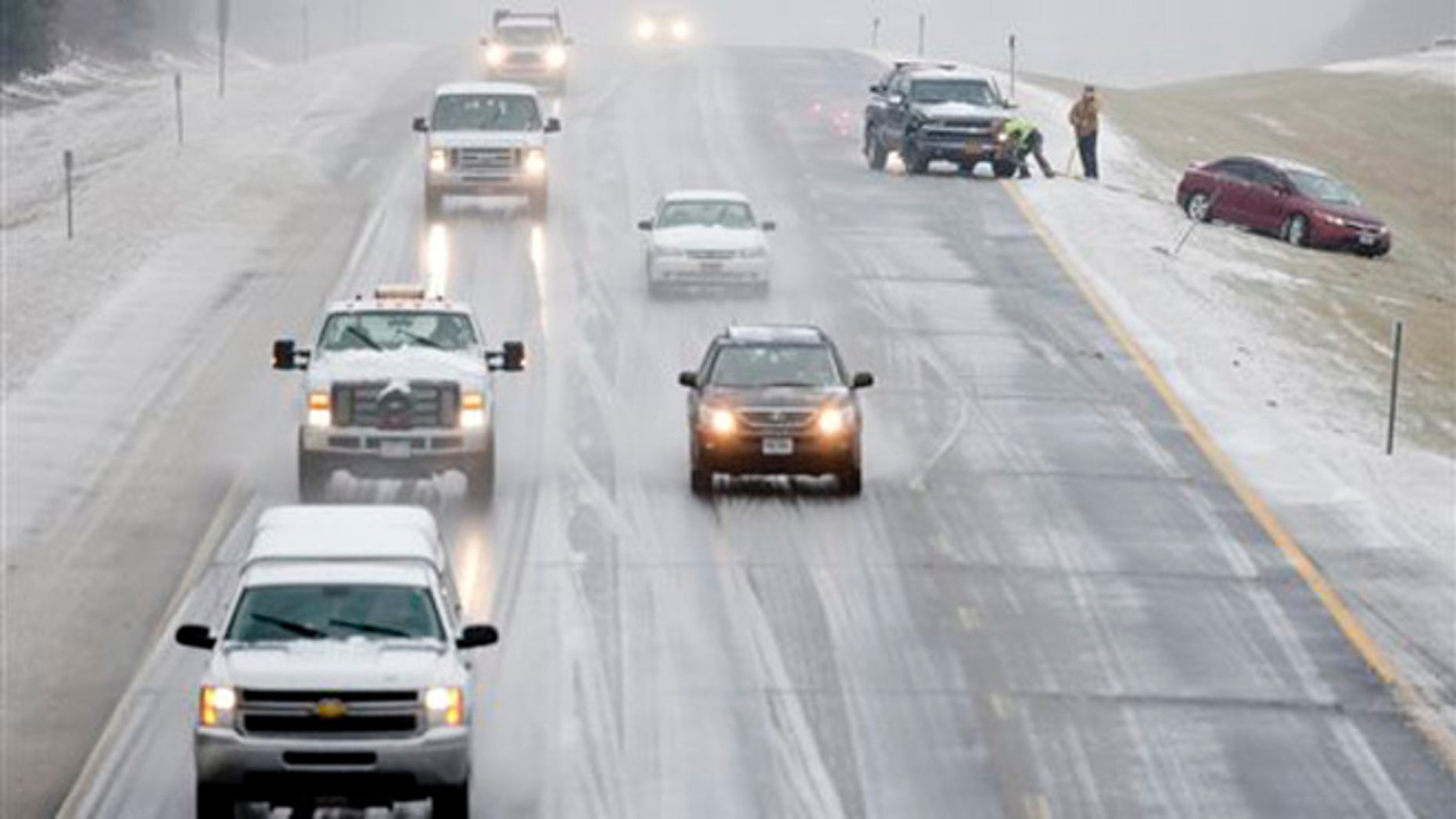 A vehicle is pulled from the median on Interstate 90 on Tuesday, Dec. 29, 2015, in East Greenbush, N.Y. Snow, sleet, freezing rain and gusty winds are creating treacherous driving conditions across upstate New York as eastern parts of the state receive their first severe weather of the winter season. (AP Photo/Mike Groll)