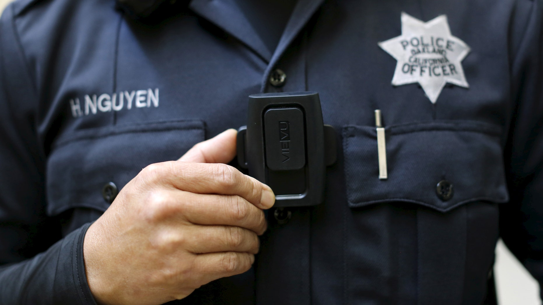 File photo - Oakland Police Department officer Huy Nguyen mounts a Portable Digital Recording Device, a body camera designed to record both audio and video in the field, at the police headquarters in Oakland, California April 14, 2015. (REUTERS/Robert Galbraith)