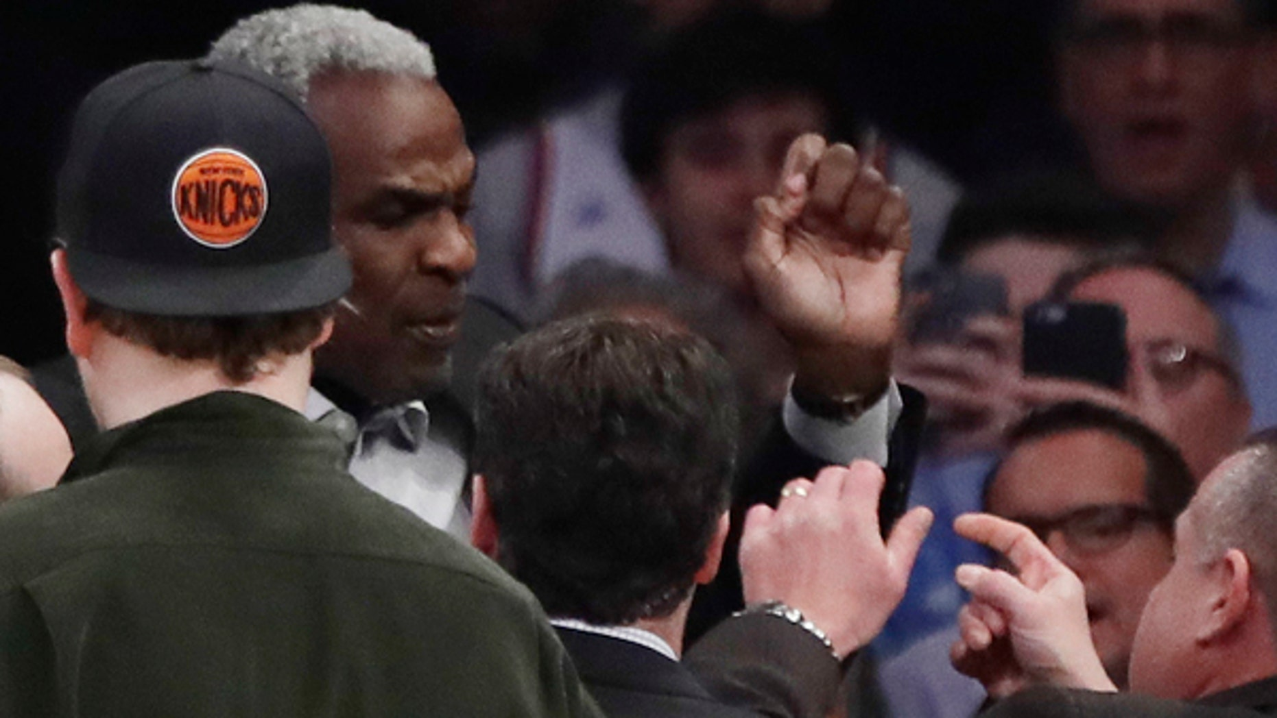 Charles Oakley is confronted by security personnel at Madison Square Garden during a Knicks game.