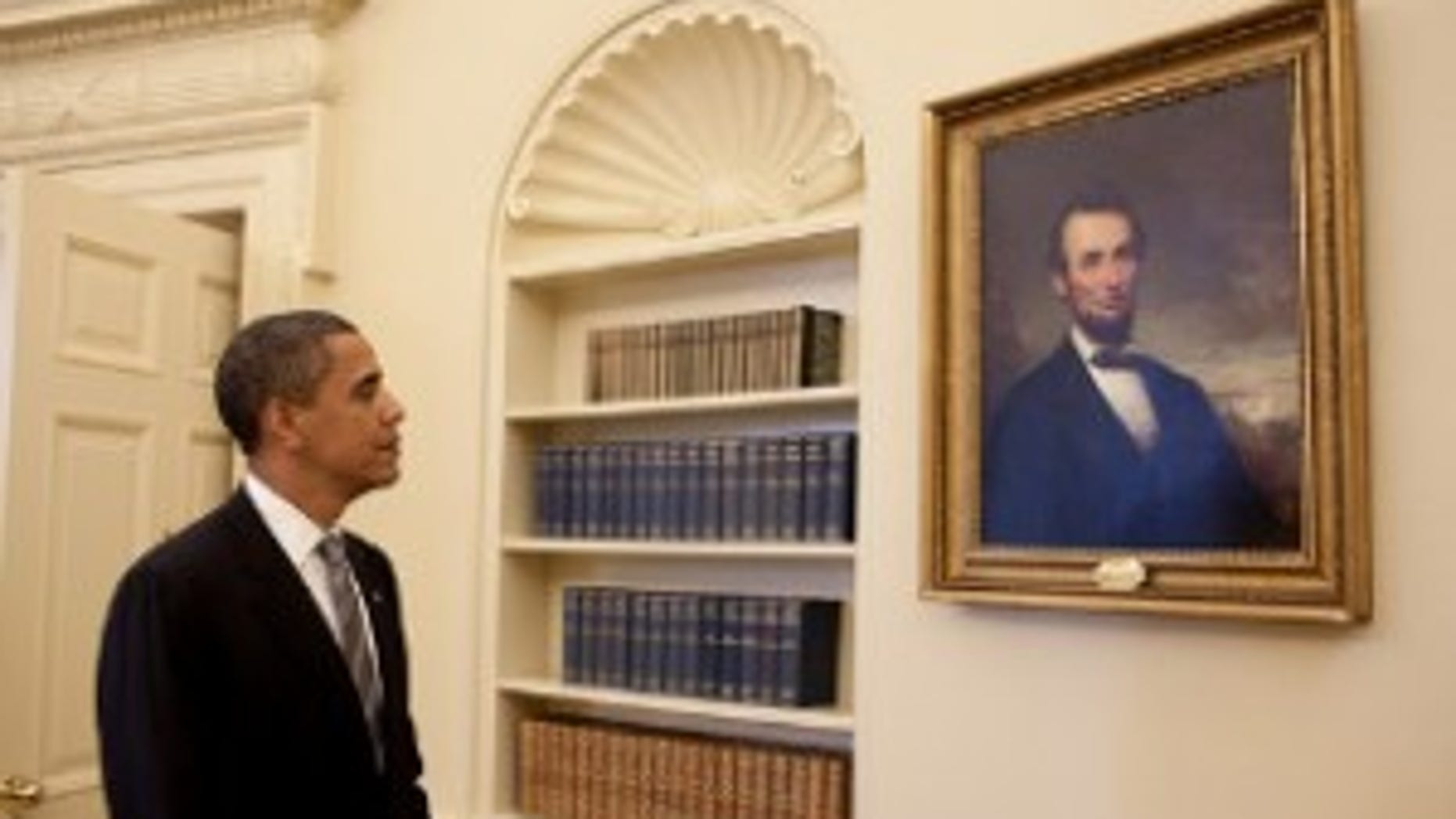 President Obama looks at a portrait of Abraham Lincoln in the Oval Office/White House Photo