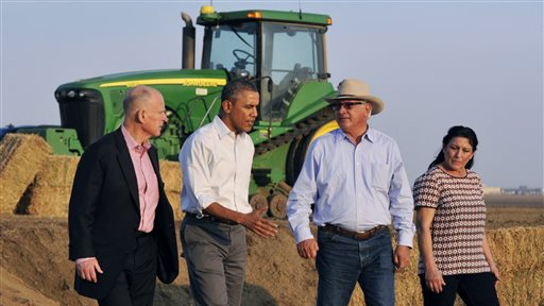President Barack Obama, second from left, walks and chats with Joe De Bosque, second from right, and his wife Maria Gloria De Bosque, far right, while California governor Jerry Brown walks at the far left, addressing drought issues on the couple's farmland south of Los Banos, Calif. on Friday, Feb. 14, 2014. (AP Photo/The Fresno Bee, Eric Paul Zamora)