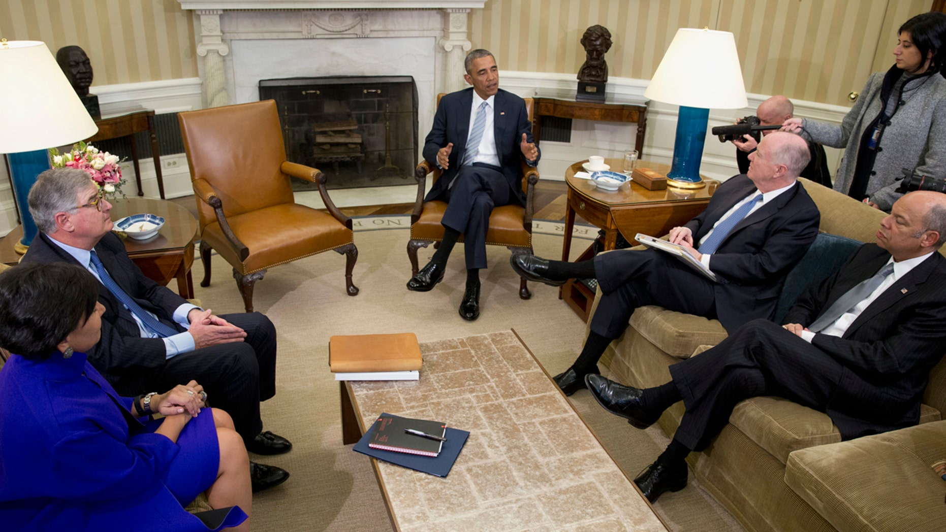 FILE - In this Feb. 17, 2016, file photo, President Barack Obama, joined by from left, Commerce Secretary Penny Pritzker, former IBM CEO Sam Palmisano, former National Security Adviser Tom Donilon, and Homeland Security Secretary Jeh Johnson, talks to media in the Oval Office of the White House, in Washington.