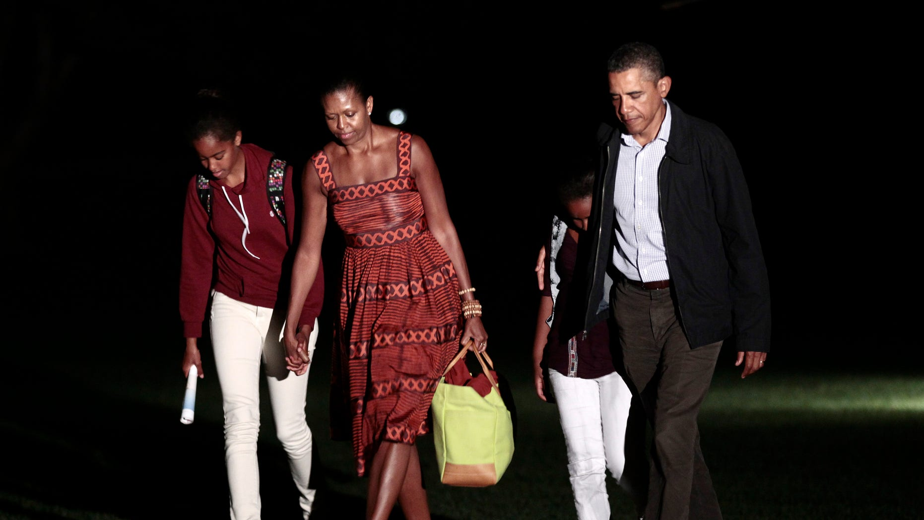 President Obama, first lady Michelle Obama and their daughters Sasha and Malia, far left, walk across the South Lawn of the White House in Washington, Friday, Aug., 26, 2011, after a family vacation on Martha's Vineyard.
