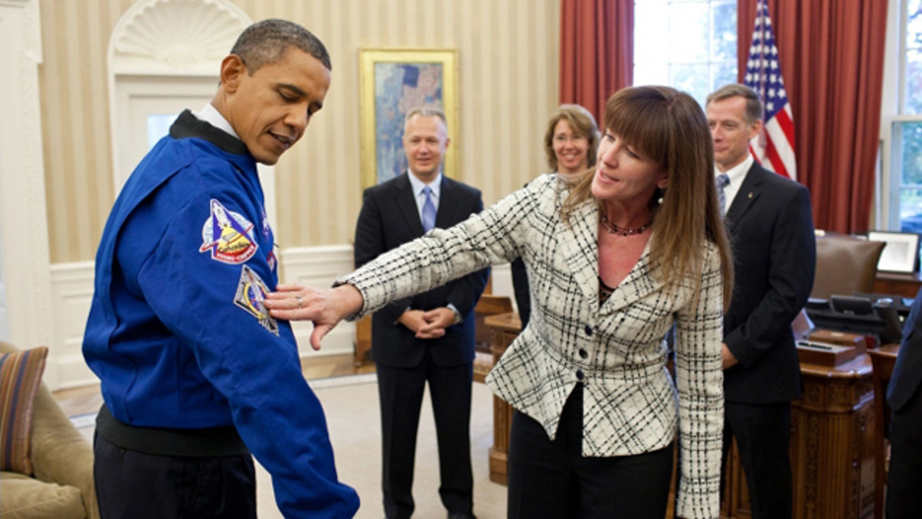 Nov. 1, 2011: Janet Kavandi, Director of Flight Crew Operations at Johnson Space Center, presents President Obama with a jacket during a drop by with the crew of the Space Shuttle Atlantis in the Oval Office.