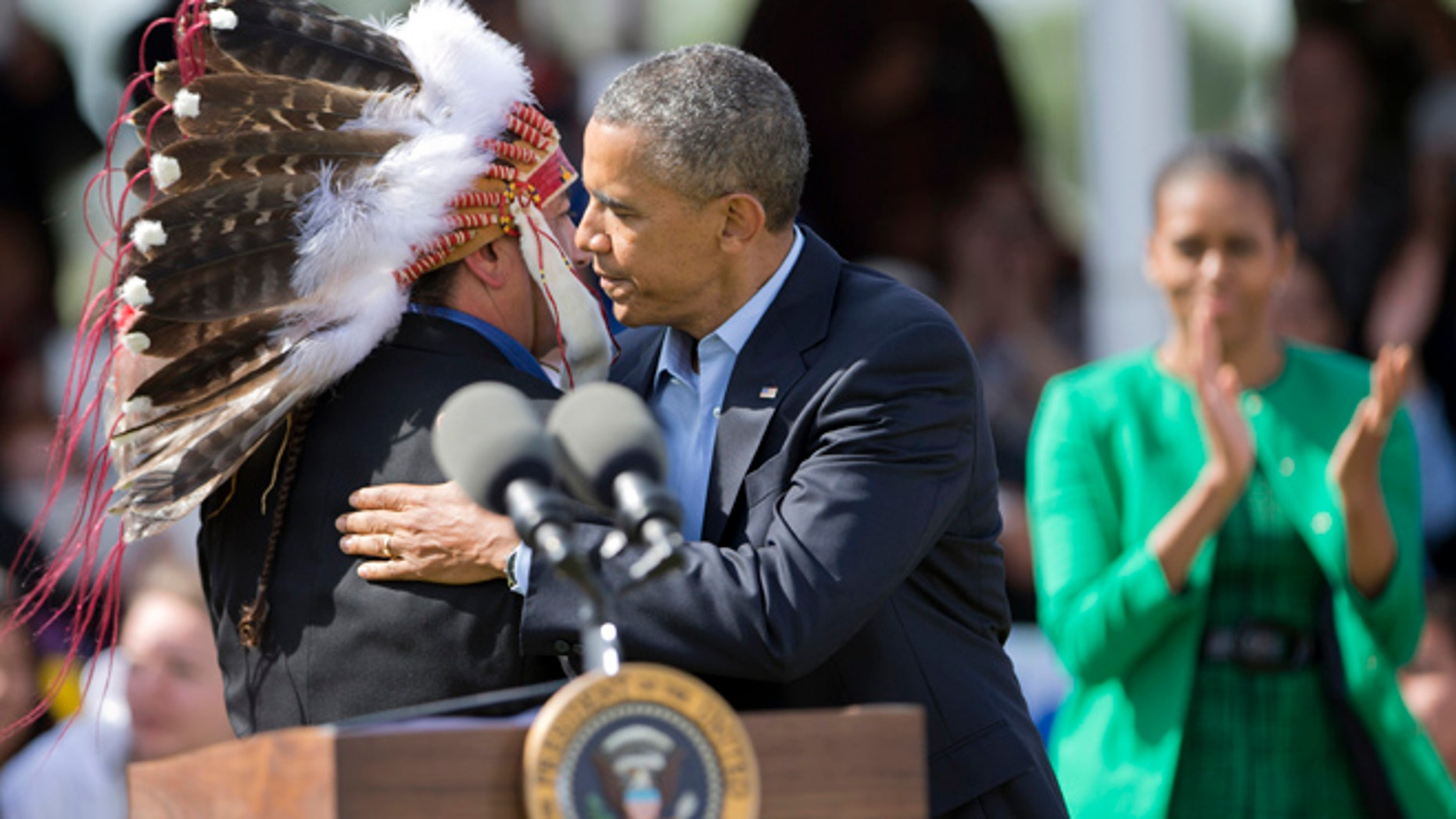 June 13, 2014: President Obama embraces Standing Rock Sioux Tribal Nation Chairman Dave Archambault II as first lady Michelle Obama watches in Cannon Ball, N.D.