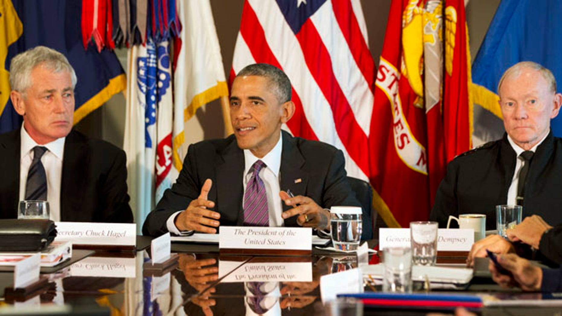 Oct. 8, 2014: President Barack Obama, flanked by Defense Secretary Chuck Hagel, left, and Joint Chiefs Chairman Gen. Martin Dempsey, speaks to the media at the conclusion of a meeting with senior military leadership