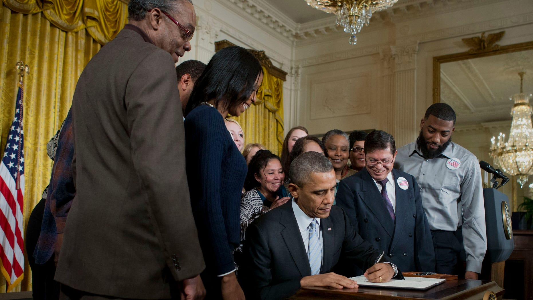 Feb. 12. 2014: President Obama, surrounded by workers, signs an executive order to raise the minimum wage for federal contract workers.