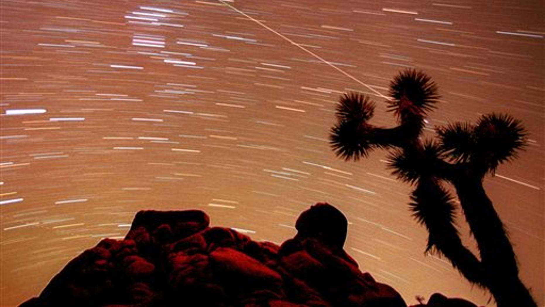 FILE - In this Nov. 17, 1998, file time exposure photo, a meteor streaks through the sky over Joshua trees and rocks at Joshua Tree National Monument in Southern California's Mojave Desert. President Barack Obama is granting national monument status to nearly 1.8 million acres of scenic California desert wilderness, including land that would connect what is now Joshua Tree National Park to other established national monuments and national parks in the area. Obama, in California this week for a fund-raising swing, plan to make the announcement Friday, Feb. 12, 2016. (AP Photo/Reed Saxon, File)