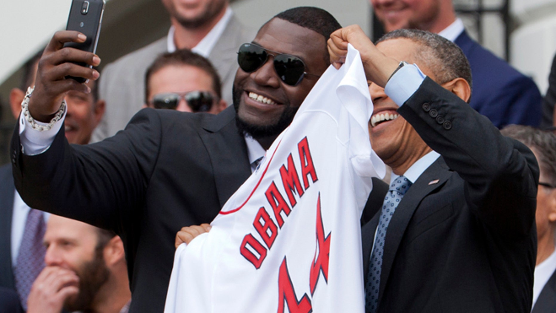 """April 1, 2014: Boston Red Sox designated hitter David  """"Big Papi"""" Ortiz, left, takes a selfie with President Obama, holding a Boston Red Sox jersey presented to the president during a ceremony on the South Lawn of the White House."""