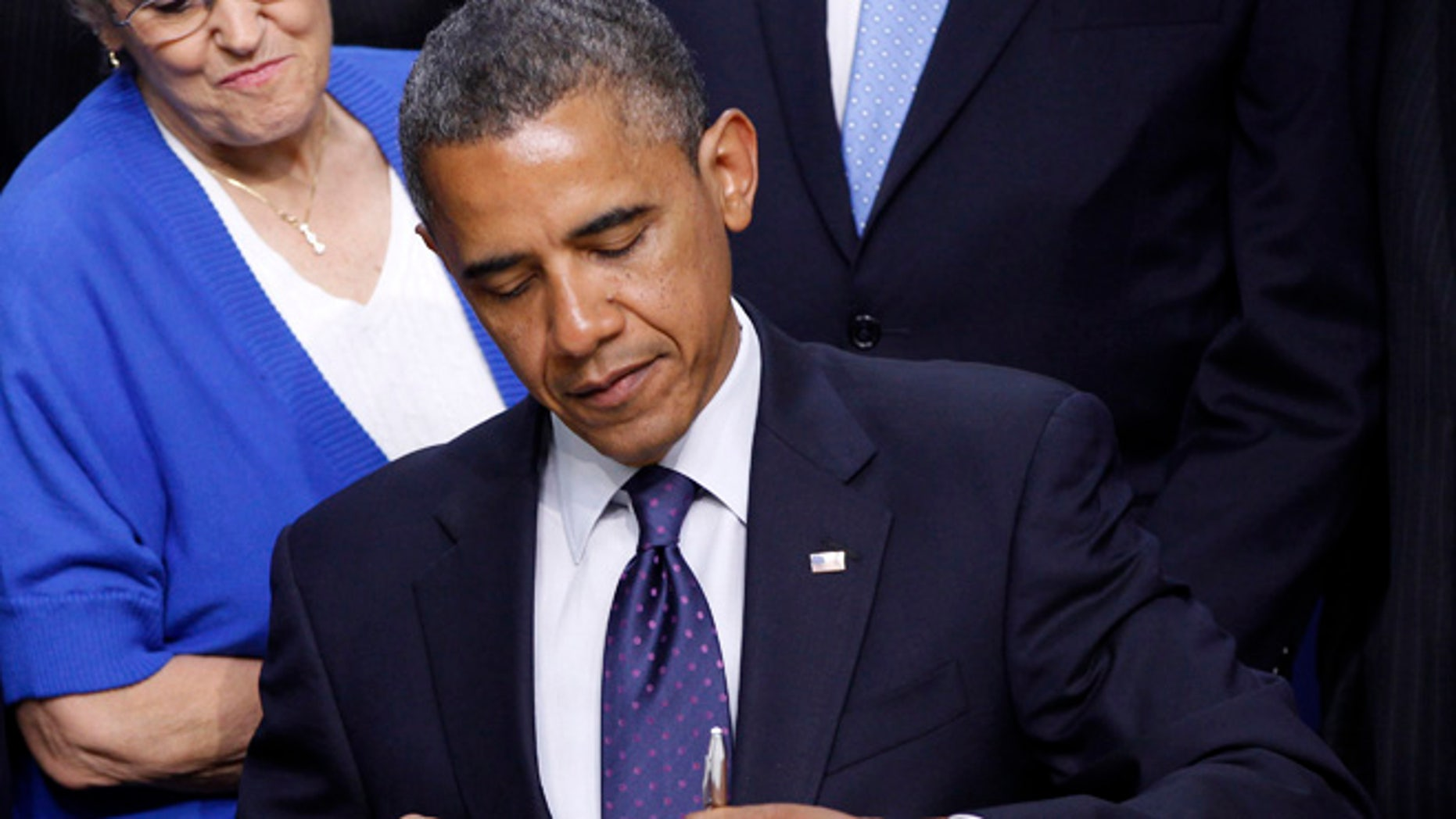 President Obama signs legislation in the Eisenhower Executive Office Building on the White House Campus in Washington.