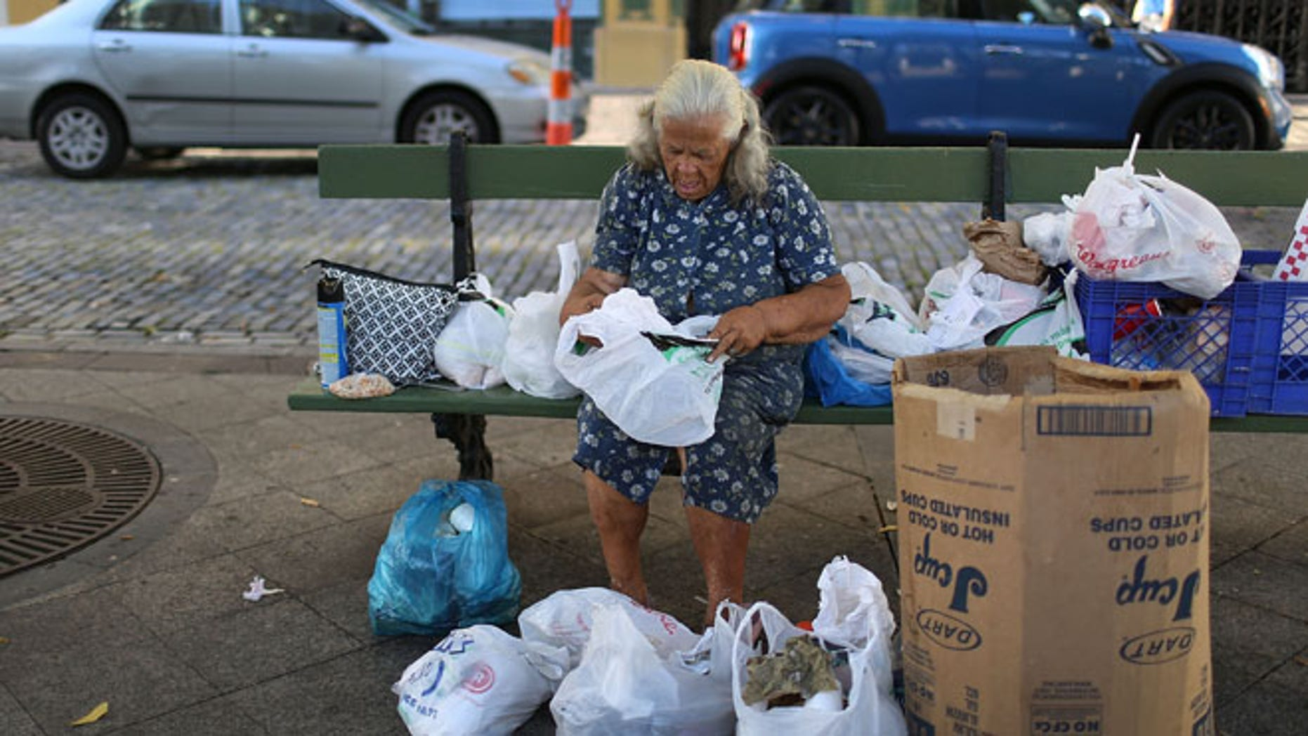 SAN JUAN, PUERTO RICO - JUNE 30:  A woman sorts through her belongings on a park bench a day after the speech Puerto Rican Governor Alejandro Garcia Padilla gave regarding the government's $72 billion debt on June 30, 2015 in San Juan, Puerto Rico.  The Governor said in his speech that the people will have to sacrifice and share in the responsibilities for pulling the island out of debt.  (Photo by Joe Raedle/Getty Images)