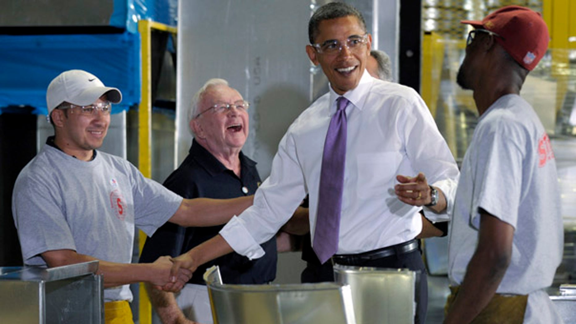 President Barack Obama shares a laugh with Stromberg Metal Works employees during a tour of the company in Beltsville, Md., Friday, Oct. 29, 2010, before speaking about the economy. Robert Gawne, Stromberg Metal Works CEO, laughs, second from left. (AP Photo/Susan Walsh)