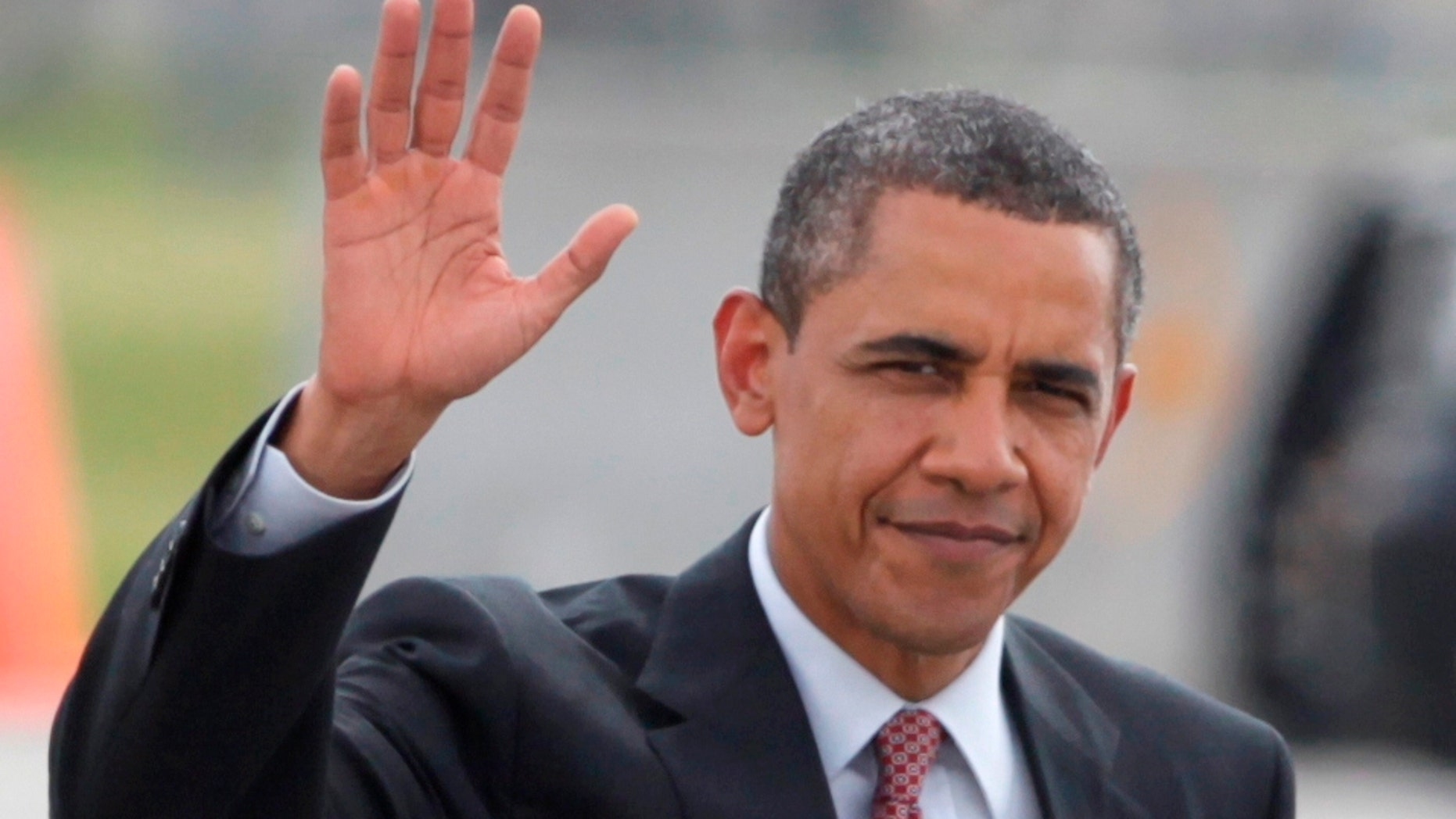 President Barack Obama waves as he walks across the tarmac to board Air Force One Thursday, June 23, 2011, in Fort Drum, N.Y., en route to New York City. (AP Photo/Carolyn Kaster)