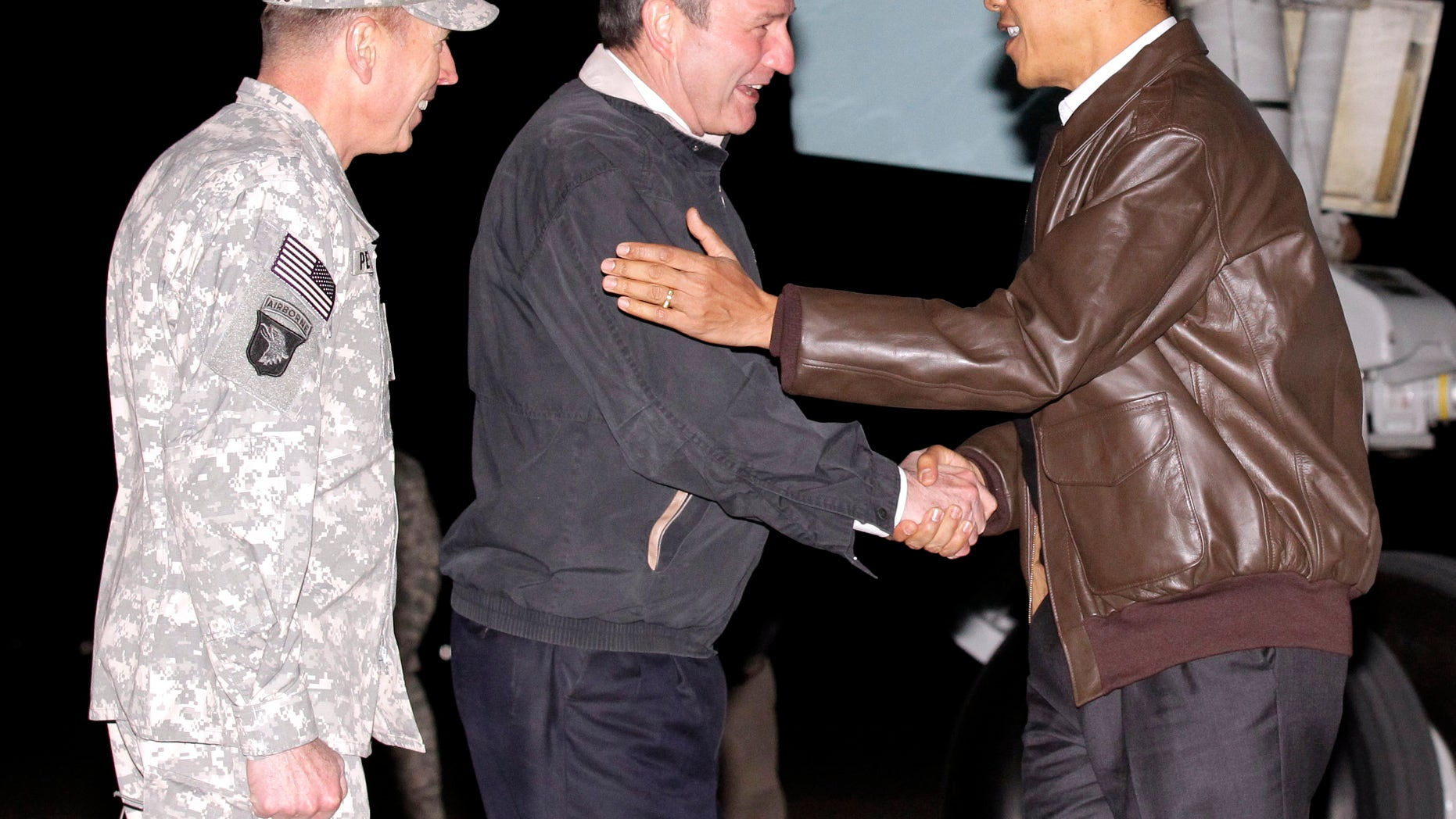President Obama is greeted by NATO Commander in Afghanistan Gen. David Petraeus, left, and US Ambassador to Afghanistan Karl W. Elkenberry, center, after stepping off Air Force One during an unannounced visit to Bagram Air Base in Afghanistan. Friday, Dec. 3, 2010. (AP)