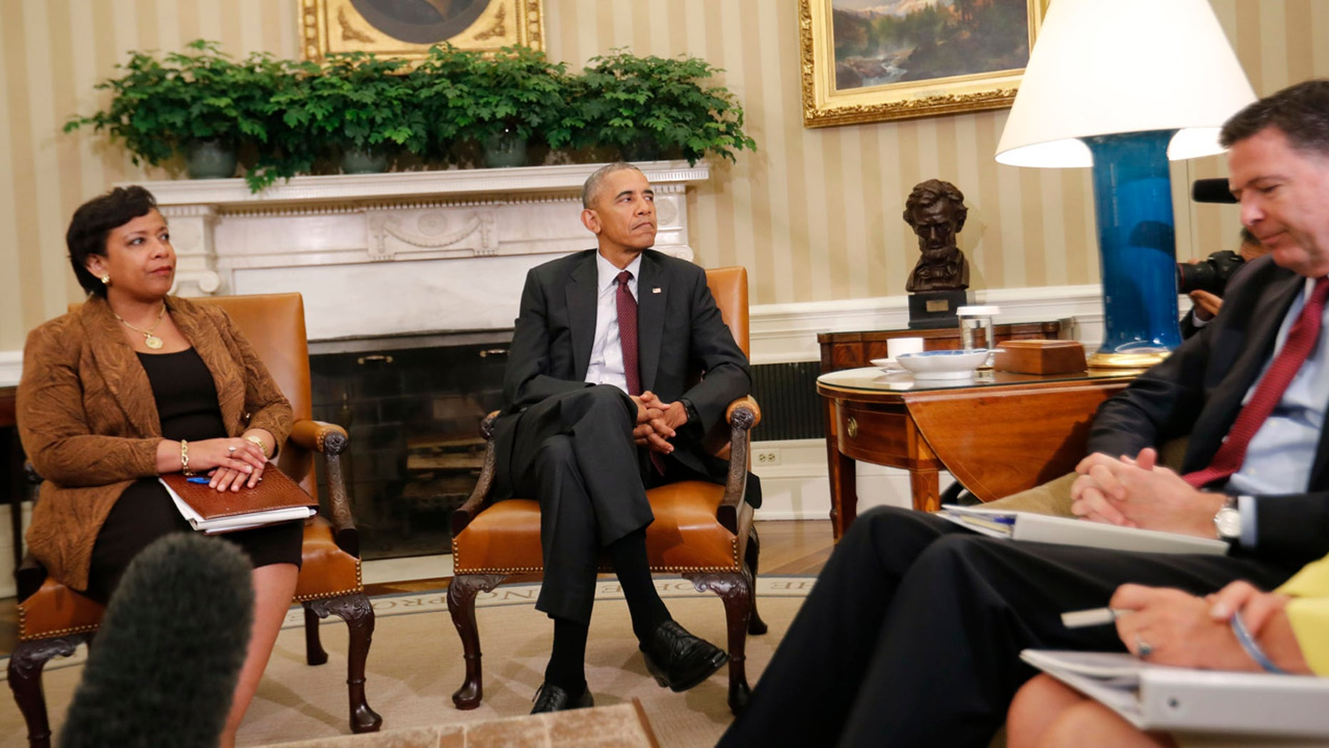 July 19, 2016: President Barack Obama, center, with Attorney General Loretta Lynch, left, and FBI Director James Comey, right, sit during their meeting in the Oval Office of the White House in Washington