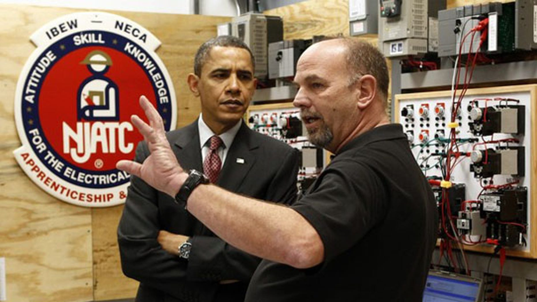 President Obama speaks with school coordinator Ralph Neidert as he tours a training center at the International Brotherhood of Electrical Workers Local 26 Headquarters in Lanham, Md., Feb. 16. (Reuters Photo)