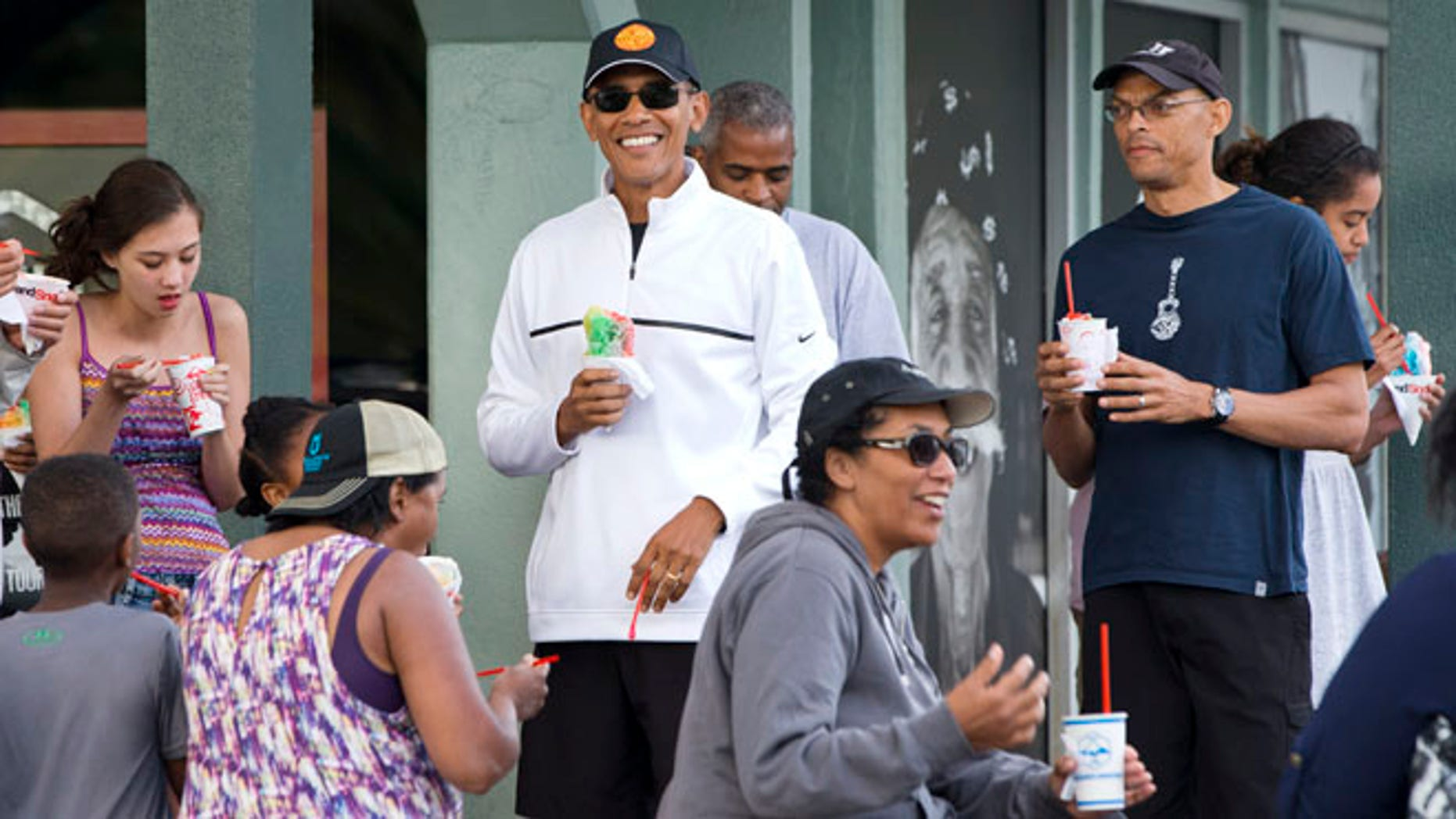 Jan. 1, 2015: President Obama smiles as he eats shave ice with friends and his daughters in Kailua, Hawaii.