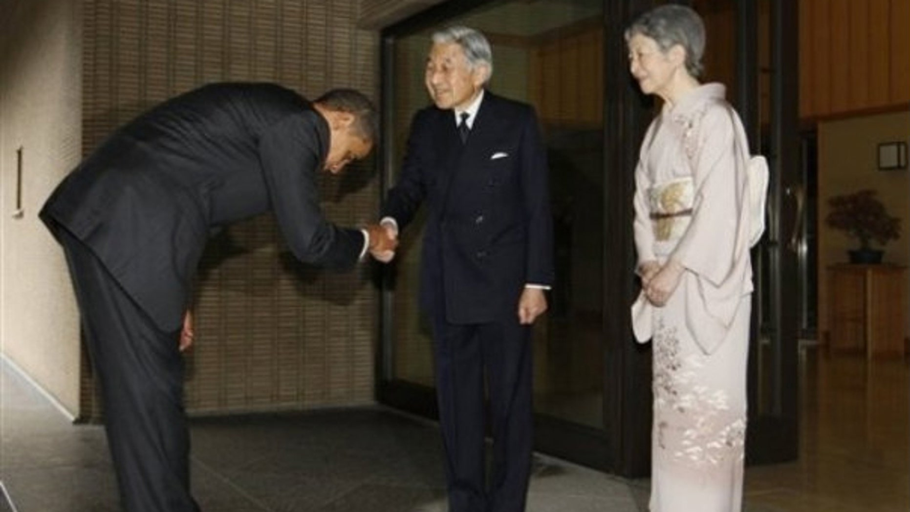 The president bows as he is greeted by Japanese Emperor Akihito and Empress Michiko as he arrives at the Imperial Palace in Tokyo (AP Photo)
