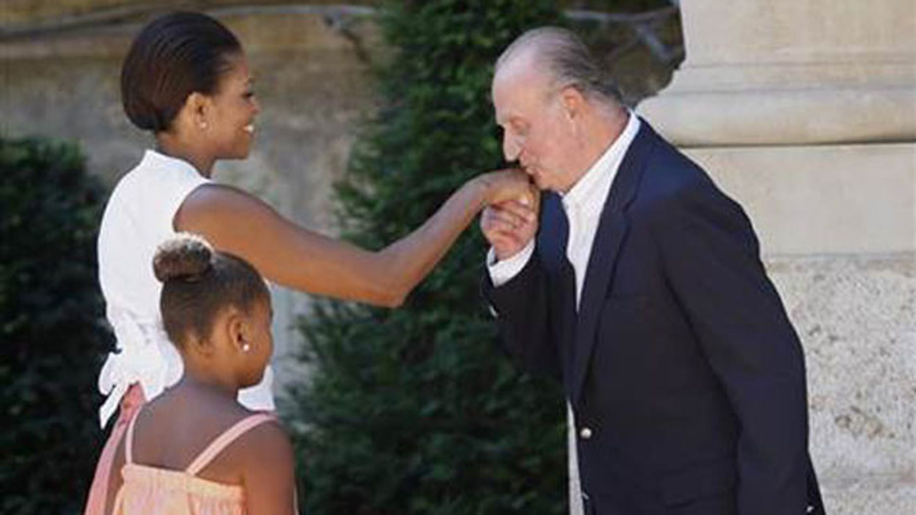 Aug. 8, 2010: First lady Michelle Obama greets Spain's King Juan Carlos, as her daughter Sasha watches.