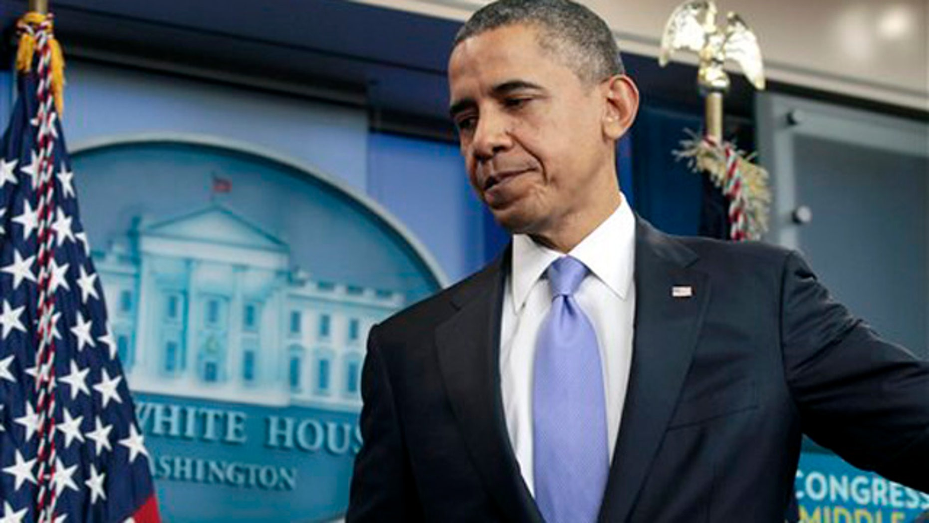 Dec. 8, 2011: President Obama leaves a news conference in the White House briefing room in Washington.