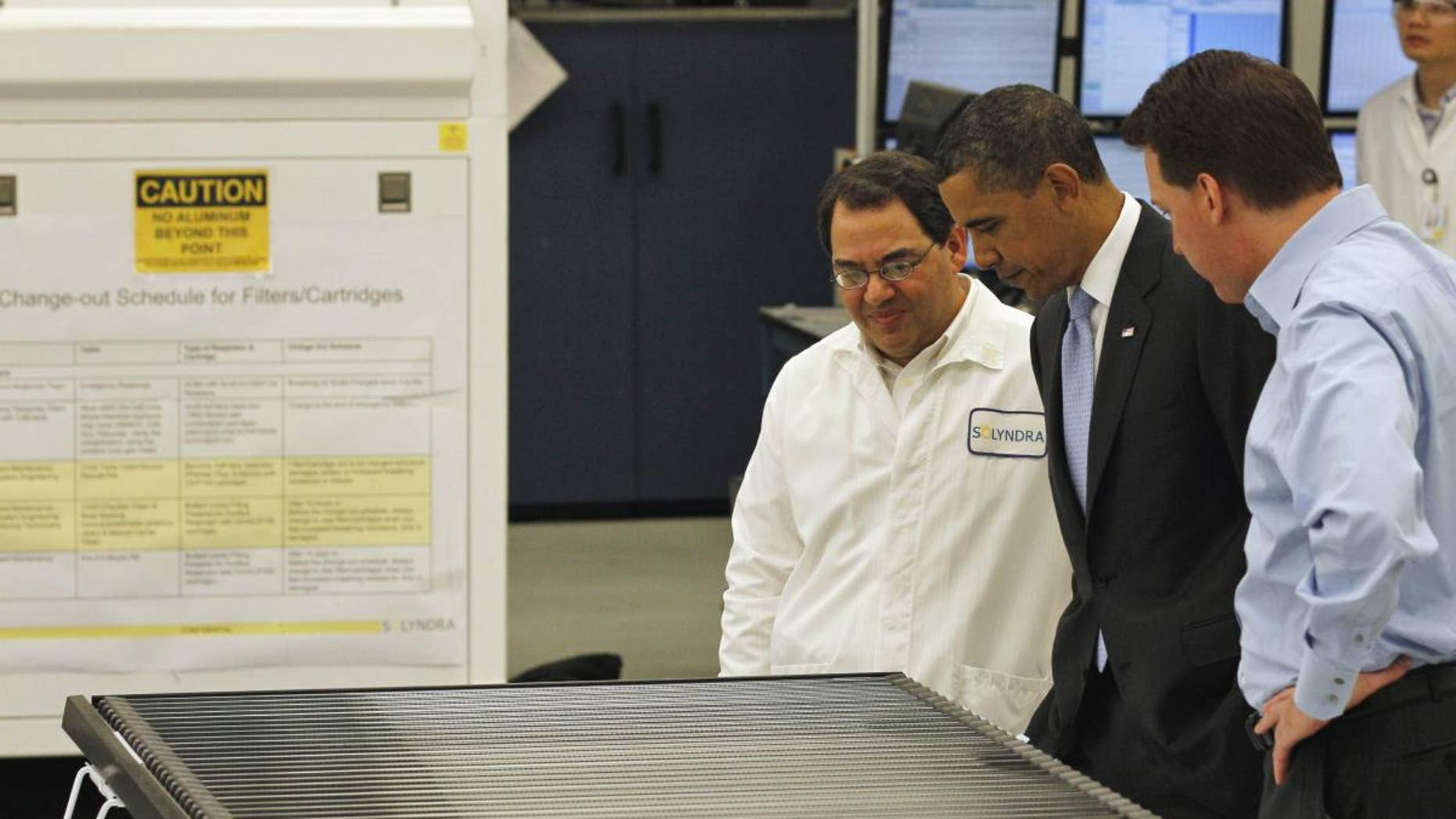 President Barack Obama, accompanied by Solyndra Chief executive Officer Chris Gronet, right, and Executive Vice President Ben Bierman, looks at a solar panel during a tour of Solyndra, Inc., a solar panel manufacturing facility, in Fremont, Calif. Wednesday, May 26, 2010. (AP Photo/Alex Brandon)