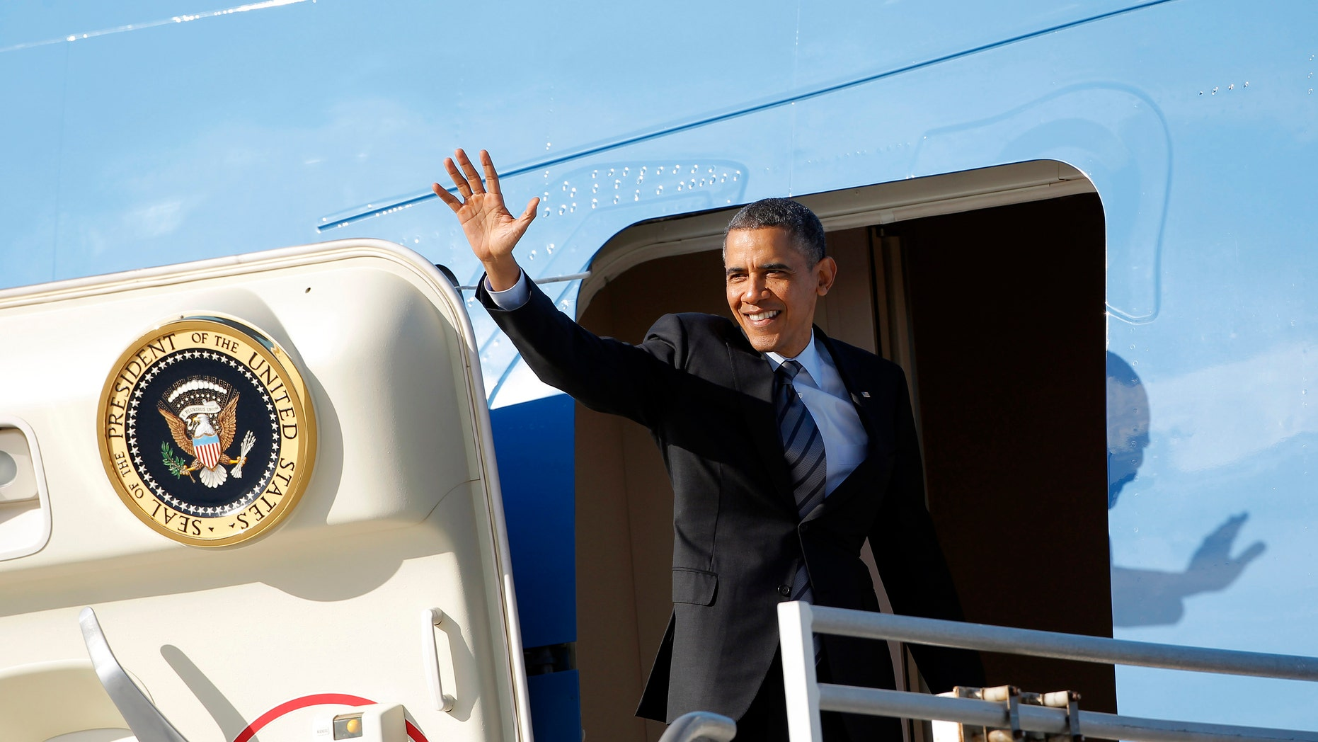 Nov 26, 2013: President Barack Obama waves as he leaves Los Angeles International Airport.