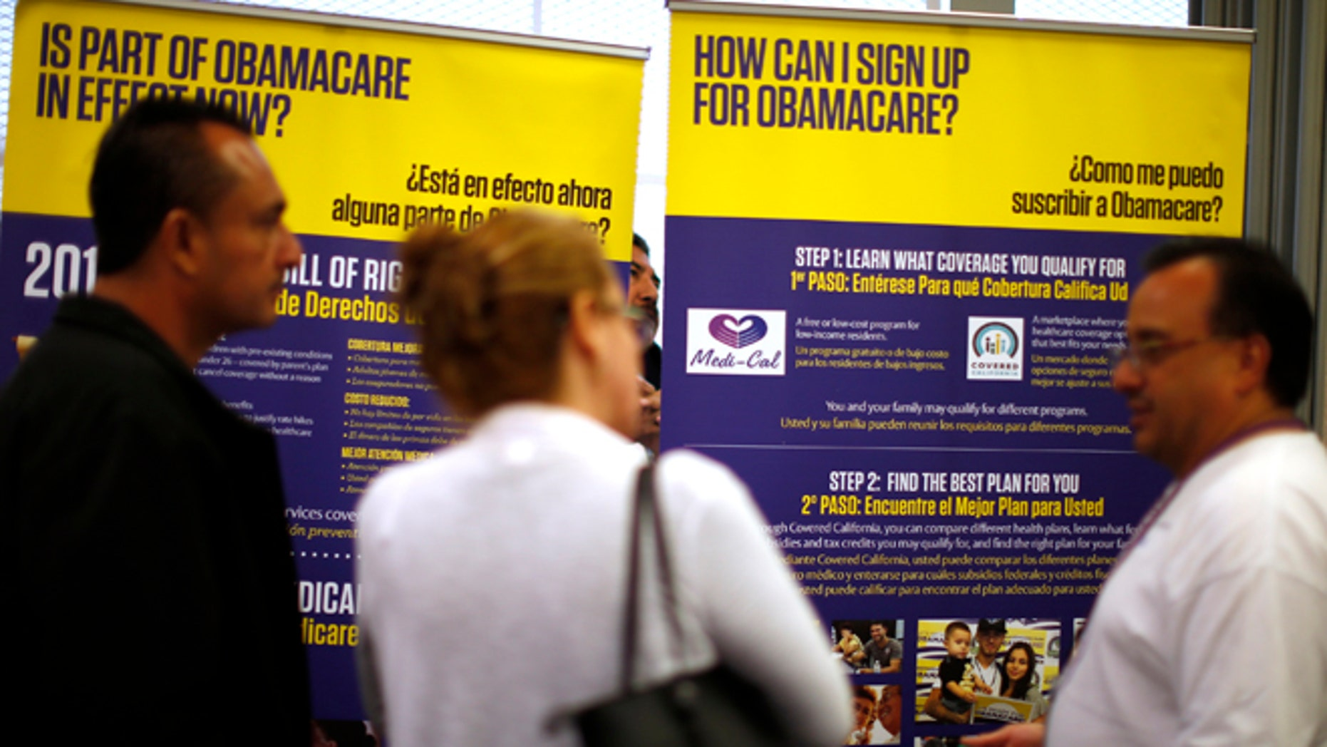 Mar. 31, 2014: Julian Gomez, right, explains ObamaCare to people at a health insurance enrollment event in Commerce, California. (Reuters)