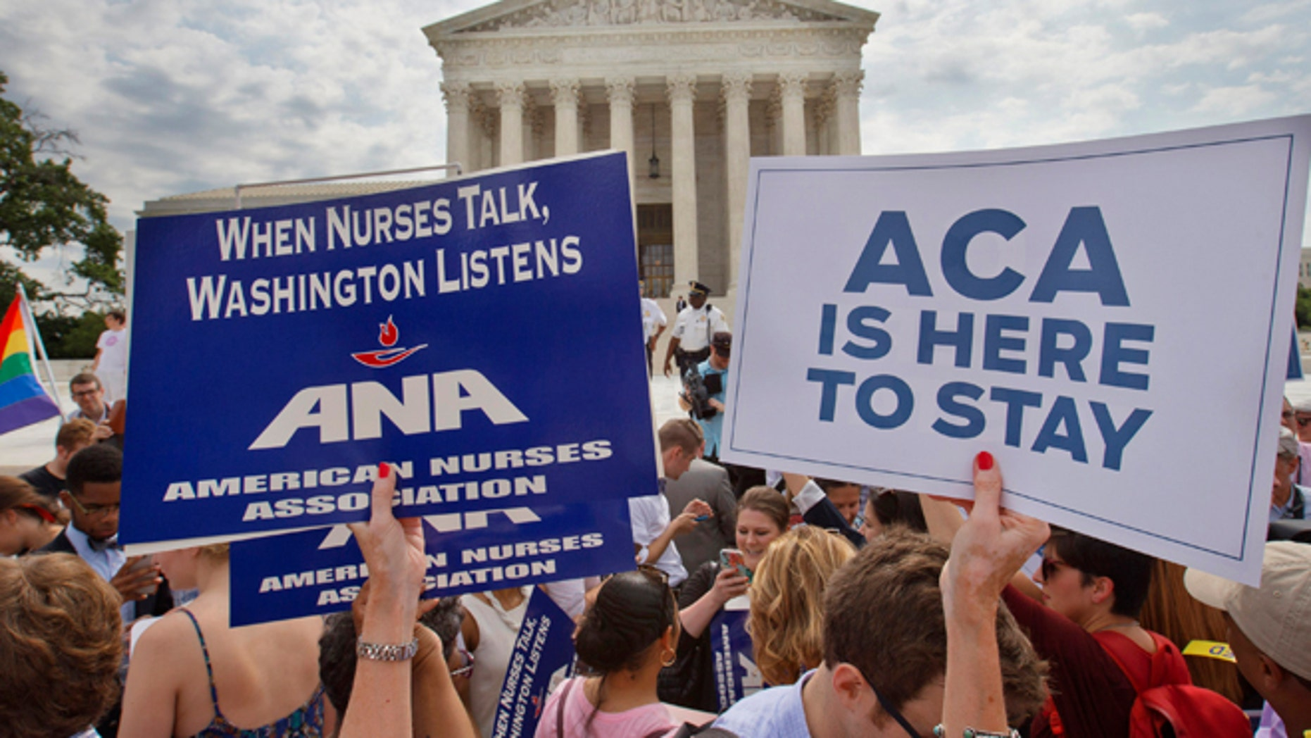 June 25, 2015: Supporters of the Affordable Care Act hold up signs as the opinion for health care is reported outside of the Supreme Court in Washington. (AP)