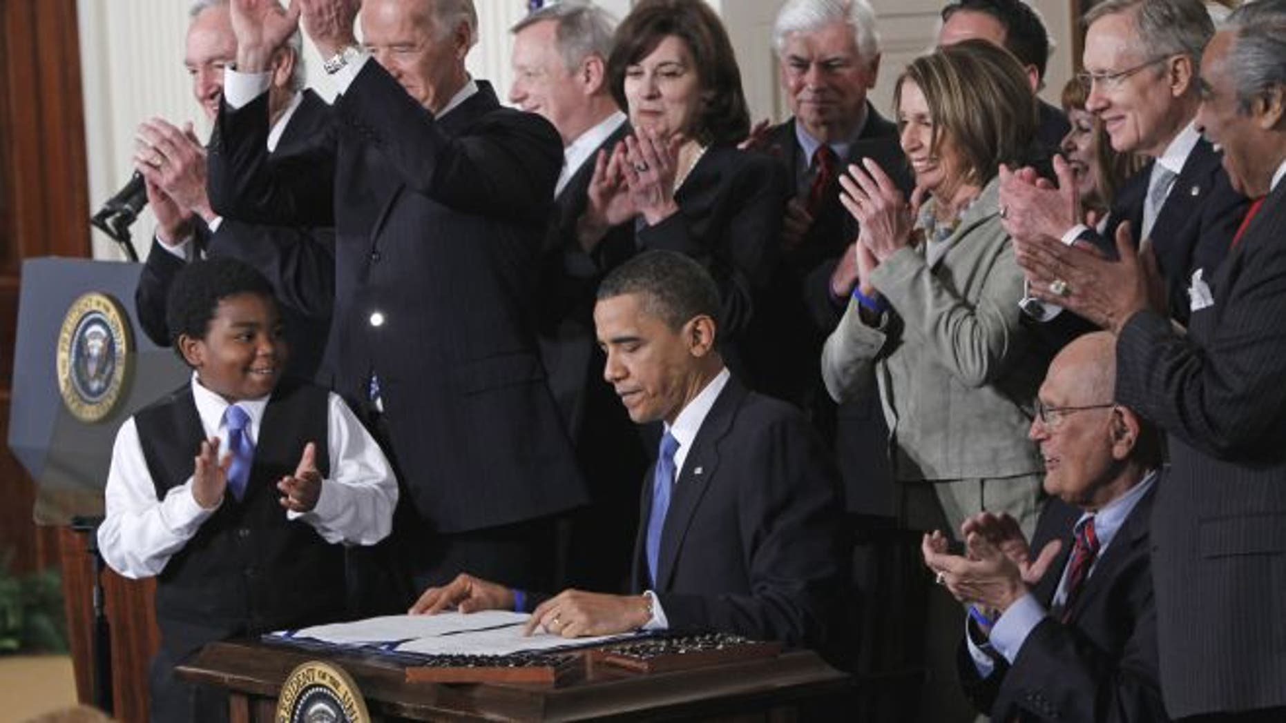 March 23, 2010: President Obama is applauded after signing the health care bill in the East Room of the White House in Washington.