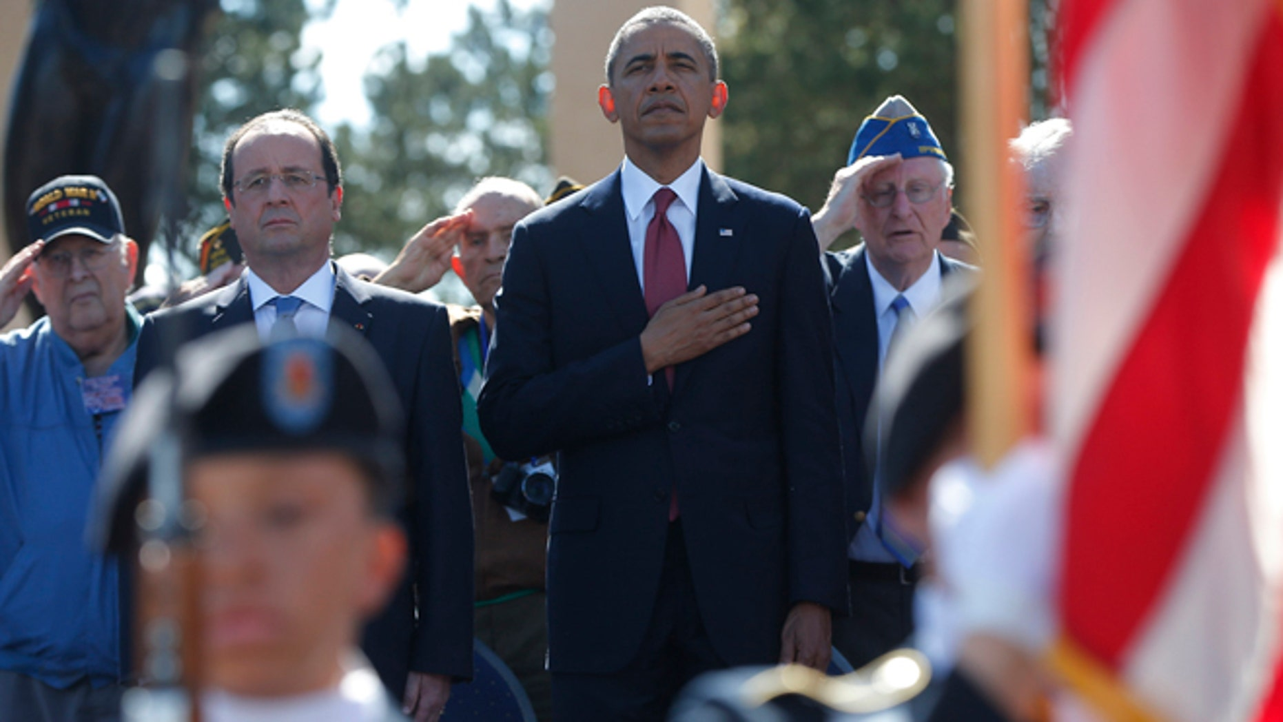 June 6, 2014: U.S. President Barack Obama, centre and French President Francois Hollande stand, during the playing of the Star Spangled Banner, at Normandy American Cemetery at Omaha Beach as he participates in the 70th anniversary of D-Day in Colleville sur Mer, in Normandy, France. (AP)