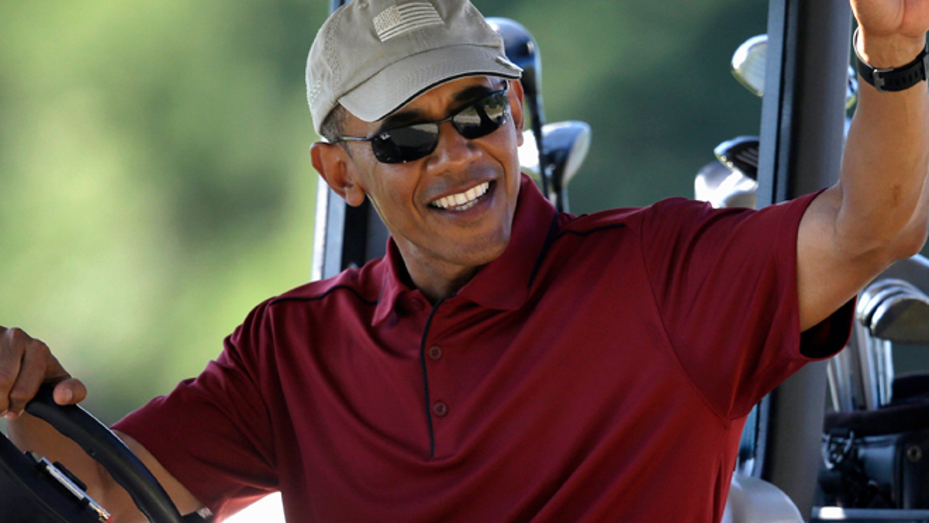 Aug. 14, 2015: President Barack Obama waves from a golf cart while golfing at Farm Neck Golf Club, in Oak Bluffs, Mass., on the island of Martha's Vineyard.