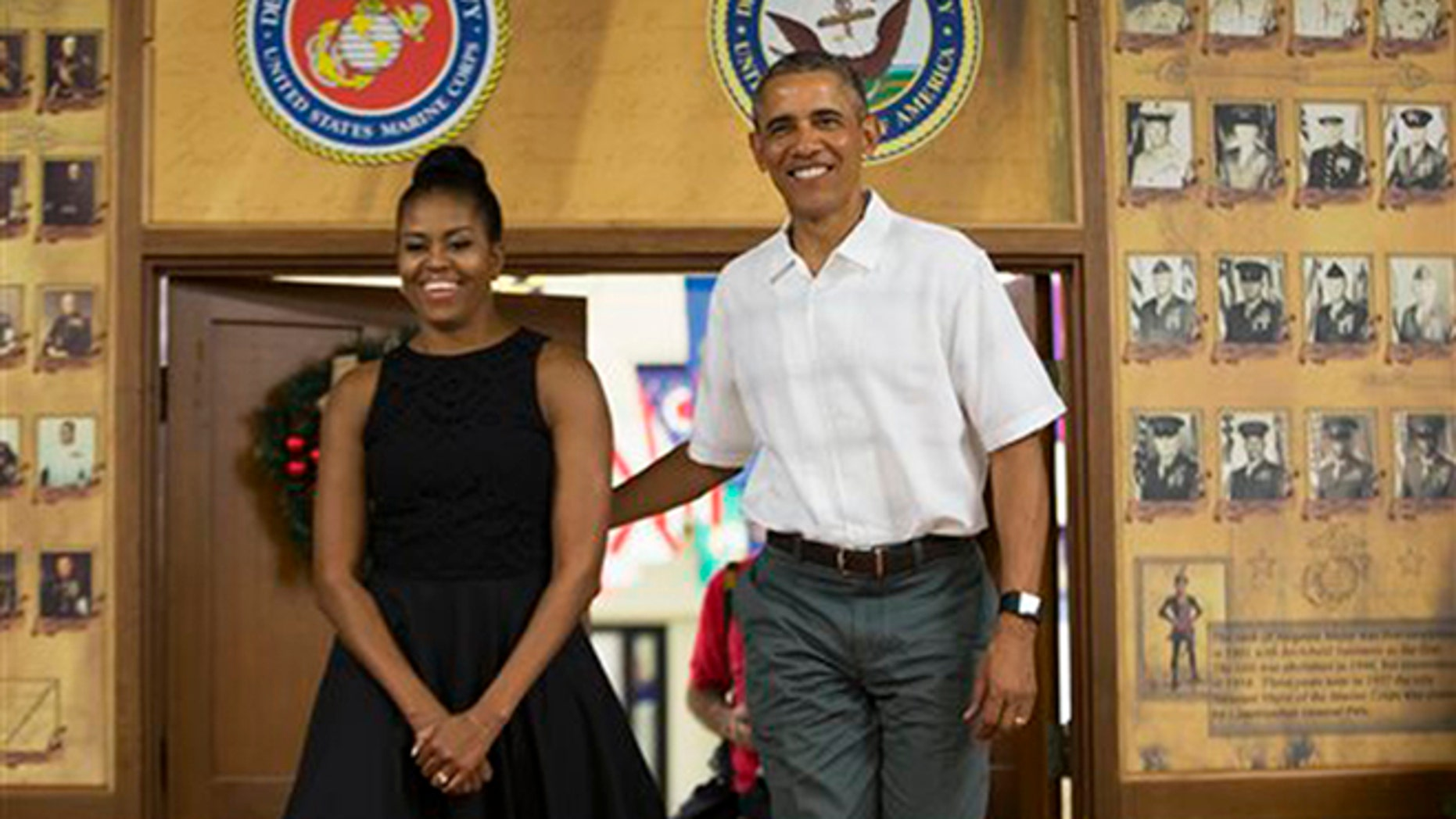 First lady Michelle Obama, left, and President Barack Obama arrive for an event to thank service members and their families at Marine Corp Base Hawaii, on Friday, Dec. 25, 2015, in Kaneohe Bay, Hawaii. (AP Photo/Evan Vucci)