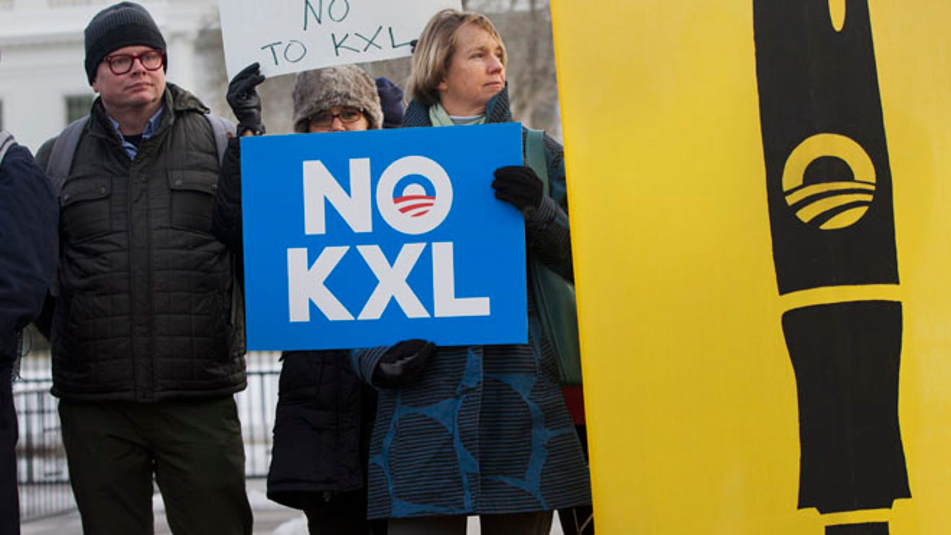 """Feb. 24, 2015: Melinda Pierce, center, with the Sierra Club, holds a """"No KXL"""" sign, next to a large poster of a pen as she gathers with other opponents of Keystone XL oil pipeline to celebrate President Barack Obama's veto of the legislation outside the White House in Washington. (AP)"""
