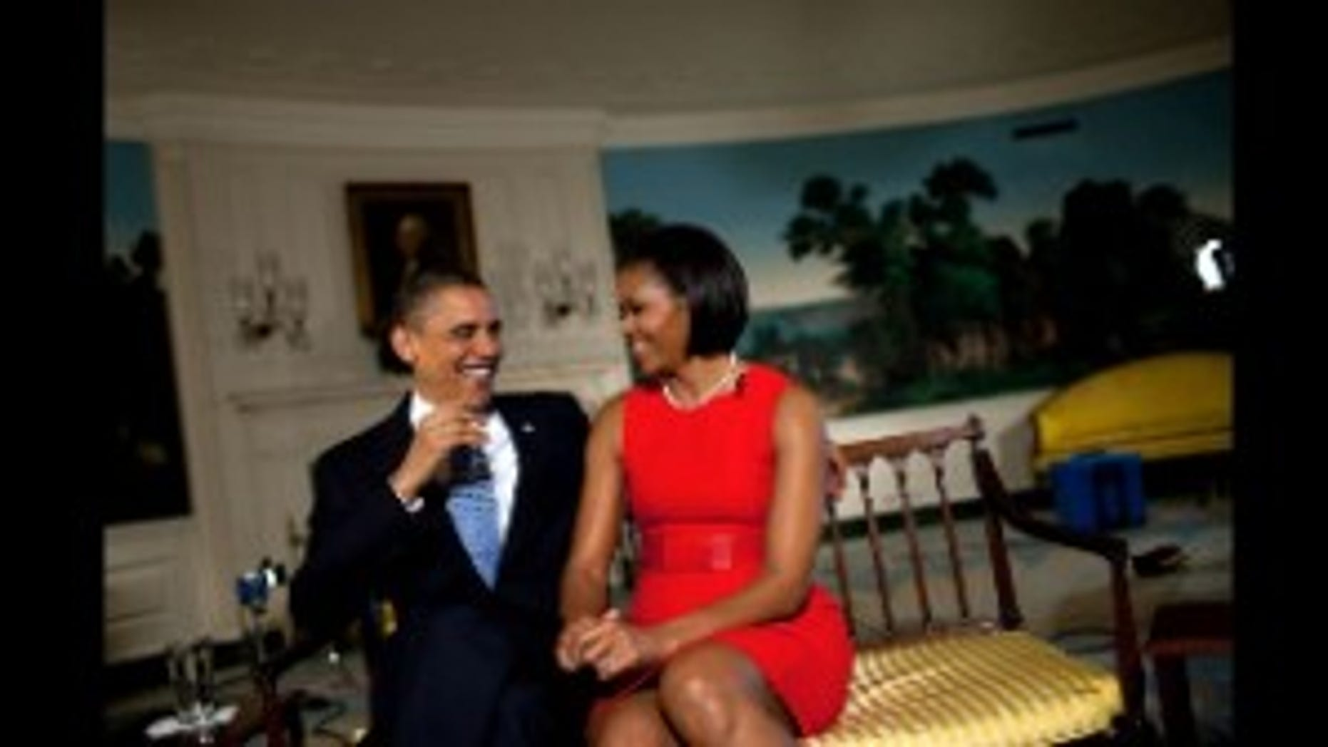 President Barack Obama and First Lady Michelle Obama laugh during a taping for the television show