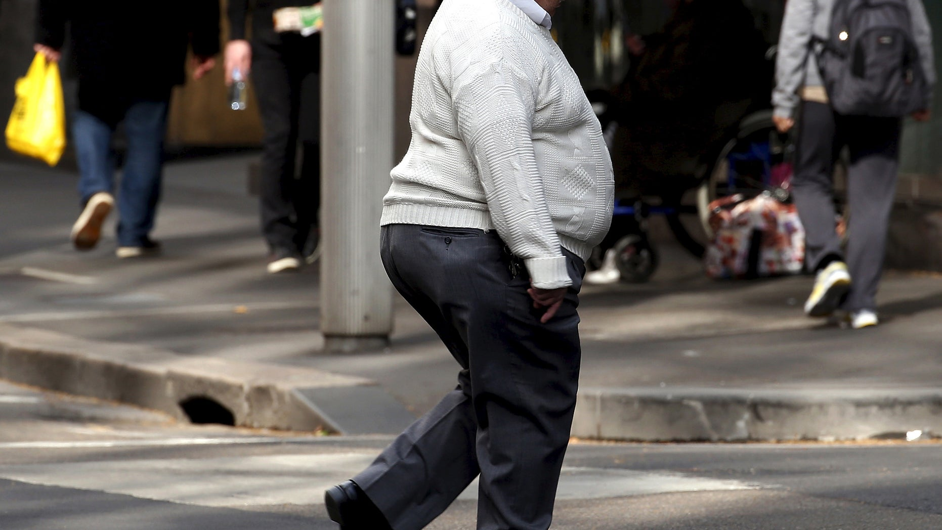 A man crosses a main road as pedestrians carrying food walk along the footpath in central Sydney, Australia, August 12, 2015. Fast food may be falling out of favour in many countries around the world but companies are making healthy profits and boldly innovating in the unlikely market of Australia. Contrary to stereotypes of a beach-going community of fitness fanatics, official data out this week showed 40 percent of Australian adults are dangerously obese and have a poor diet that includes lashings of fast food. That makes Australia a hotbed for innovation by companies including homegrown firm Domino's Pizza Enterprises Ltd, McDonald's Corp and Yum! Brands Inc's, KFC and Pizza Hut as they struggle to win over health-conscious diners in other countries. Picture taken August 12, 2015.    REUTERS/David Gray - RTX1O50L