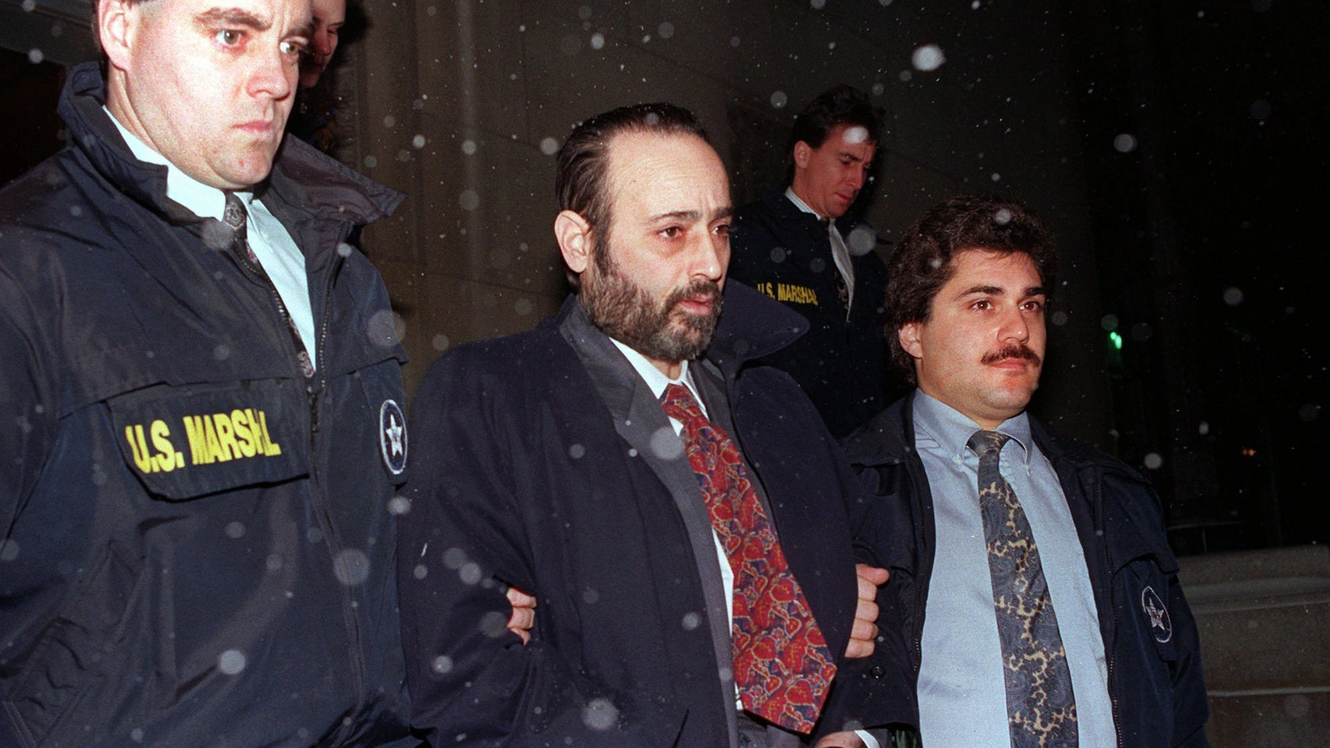 "In this Jan. 11, 1993 file photo, ""Crazy"" Eddie Antar, center, founder of the Crazy Eddie electronics store chain, is led in handcuffs after being extradited from Israel."