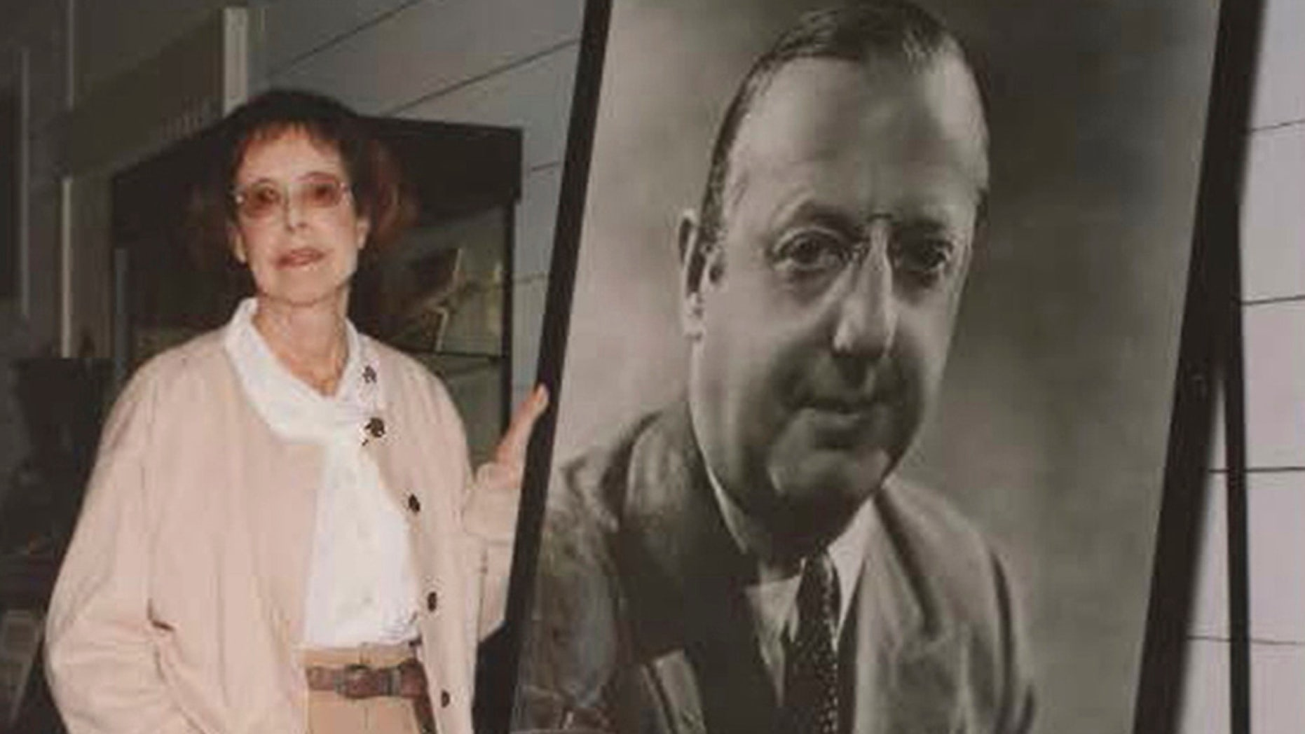 In this 2002 photo provided by Bart Bragg, author and film historian, Betty Lasky, poses with a portrait of her father, Jesse L. Lasky, at the Lasky-DeMille Barn, now the Hollywood Heritage Museum, in Los Angeles.