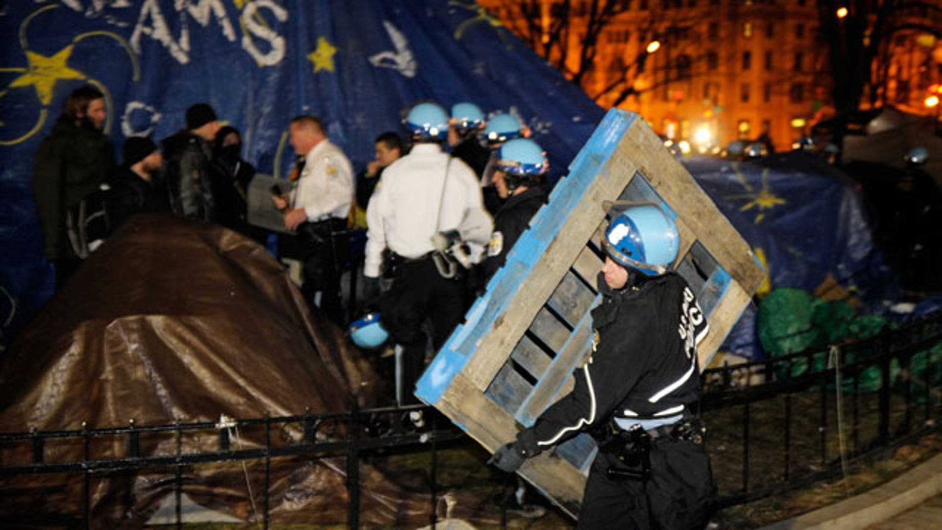 Feb. 4, 2012: A U.S. Park Police officer removes a wooden structure from an Occupy DC protestor's tent at McPherson Square in Washington.