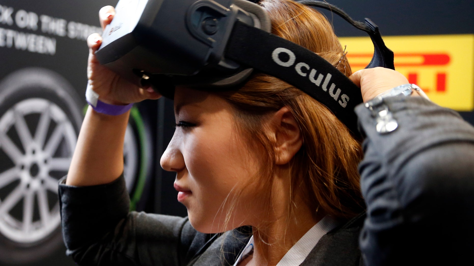 A woman puts on an Oculus virtual reality headset during preparations for the 2014 LA Auto Show in Los Angeles, California November 18, 2014. REUTERS/Lucy Nicholson