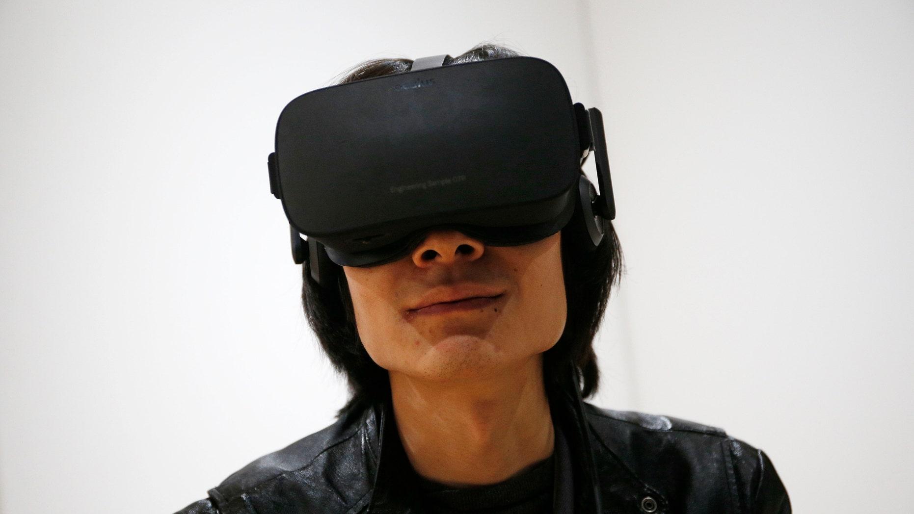 File photo - Peijun Guo wears the Oculus Rift VR headset at the Oculus booth at CES International, Wednesday, Jan. 6, 2016, in Las Vegas. (AP Photo/John Locher)