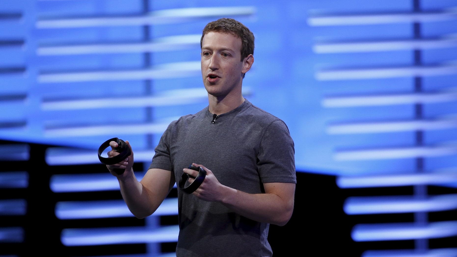 File photo - Facebook CEO Mark Zuckerberg holds a pair of the touch controllers for the Oculus Rift virtual reality headsets on stage during the Facebook F8 conference in San Francisco, California April 12, 2016. (REUTERS/Stephen Lam)