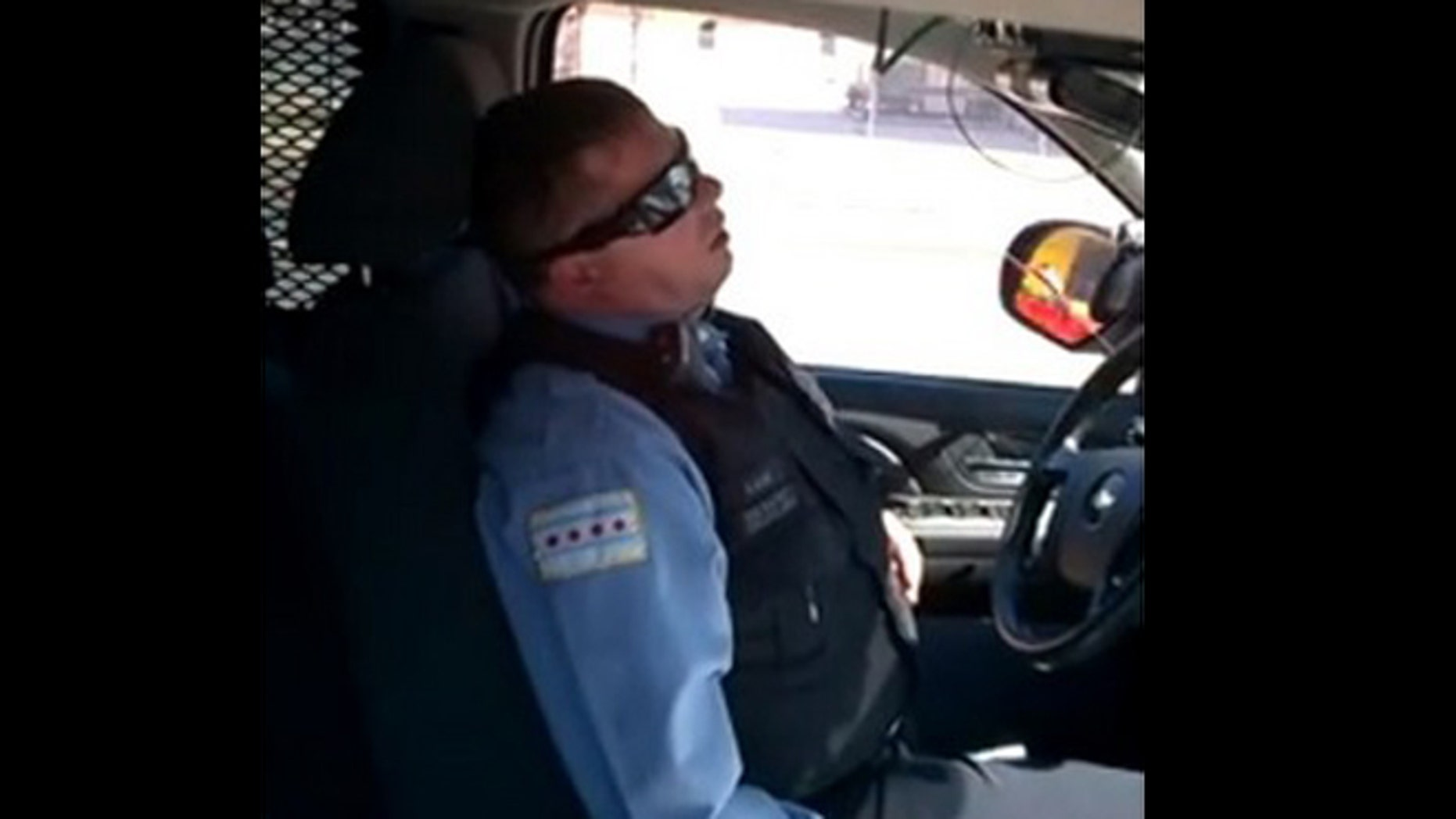 A video of a Chicago officer sleeping in his SUV parked on a busy street has gone viral.