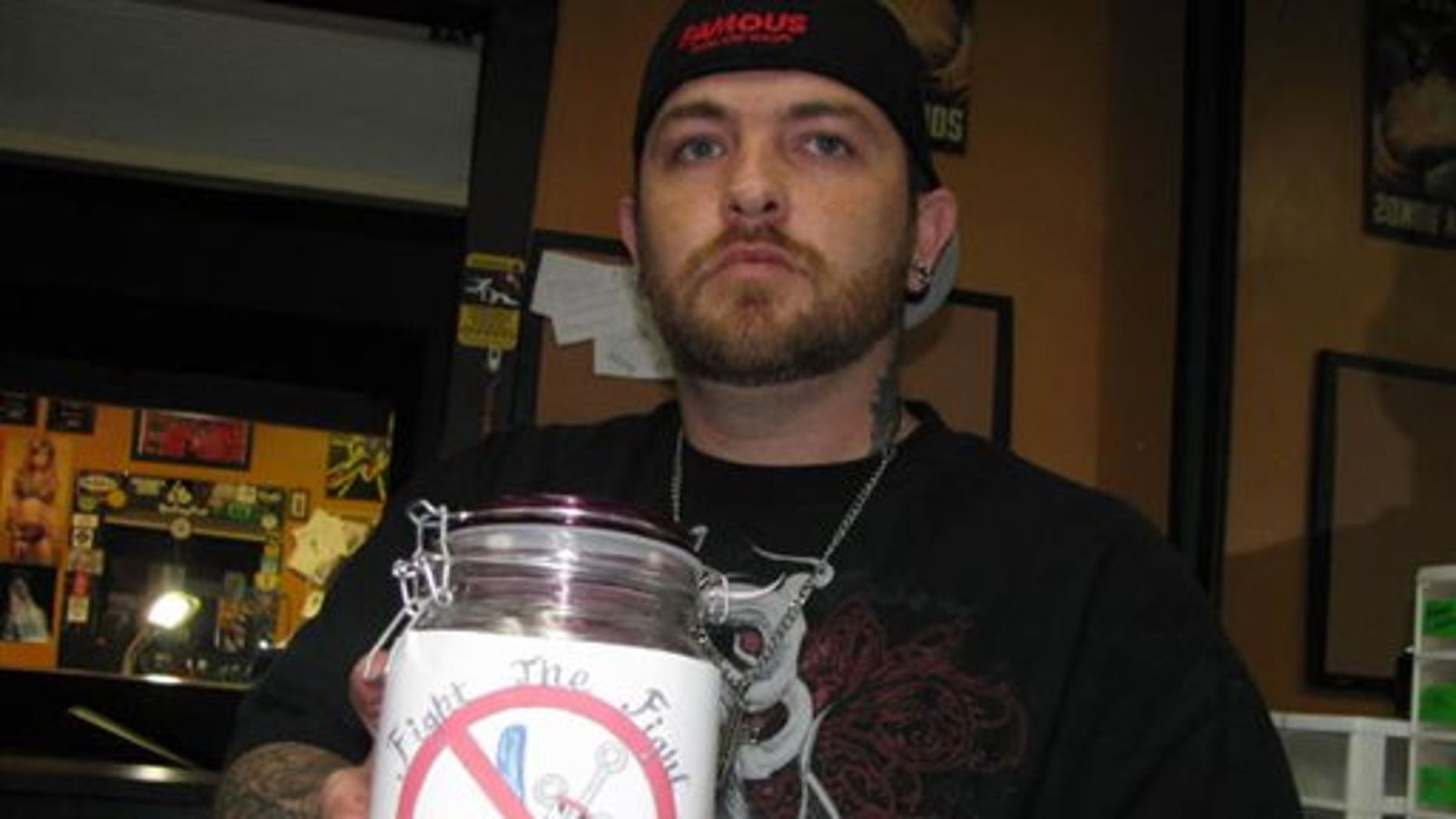 In this photo taken June 1, 2015, tattoo artist Justin Cantrell displays a fundraising jug bearing a tattoo design he created to help support recovering heroin addicts in Marion, Ohio in Marion, Ohio, after a spate of more than 30 overdoses in an 11-day period at the end of May. (AP Photo/Mitch Stacy)