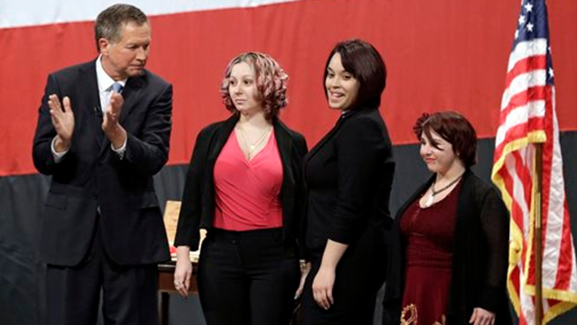 Feb. 24, 2014: Ohio Gov. John Kasich, from left, introduces Amanda Berry, Gina DeJesus and Michelle Knight during his State of the State address at the Performing Arts Center in Medina, Ohio.