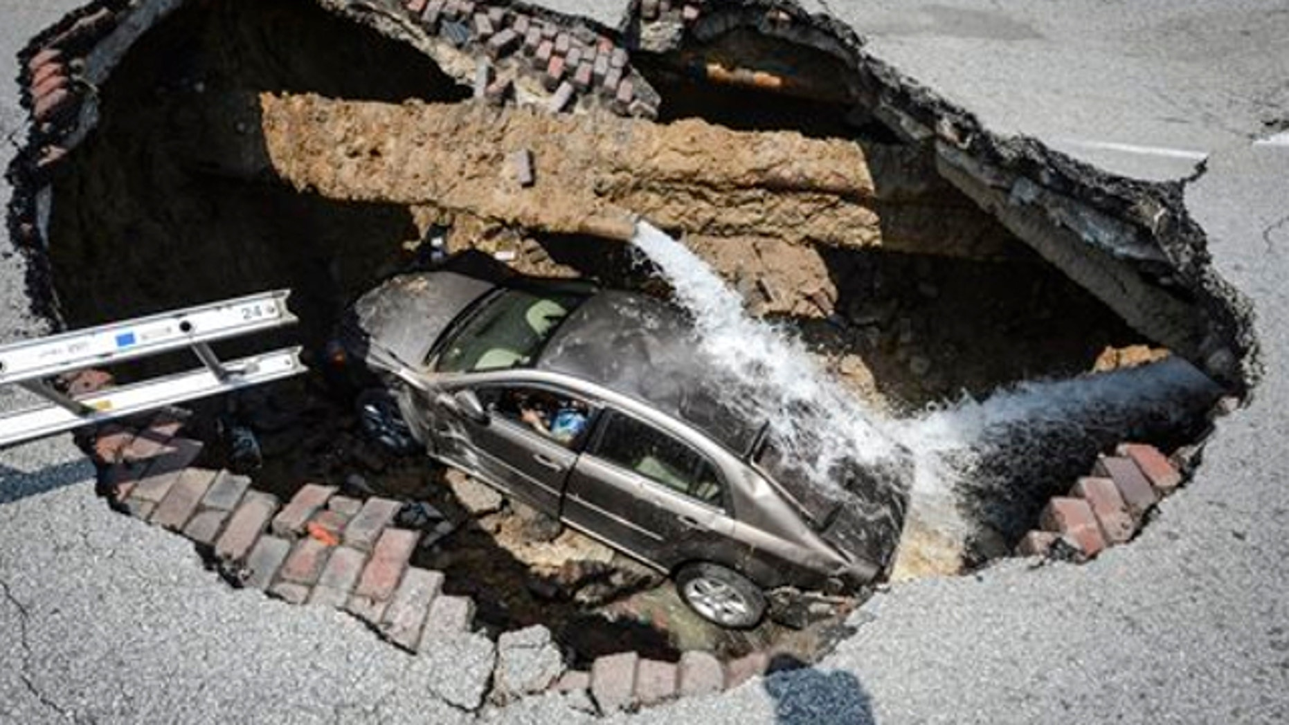 July 3, 2013: This photo provided by the Toledo, Ohio Fire and Rescue Department shows a car at the bottom of a sinkhole caused by a broken water line in Toledo, Ohio.