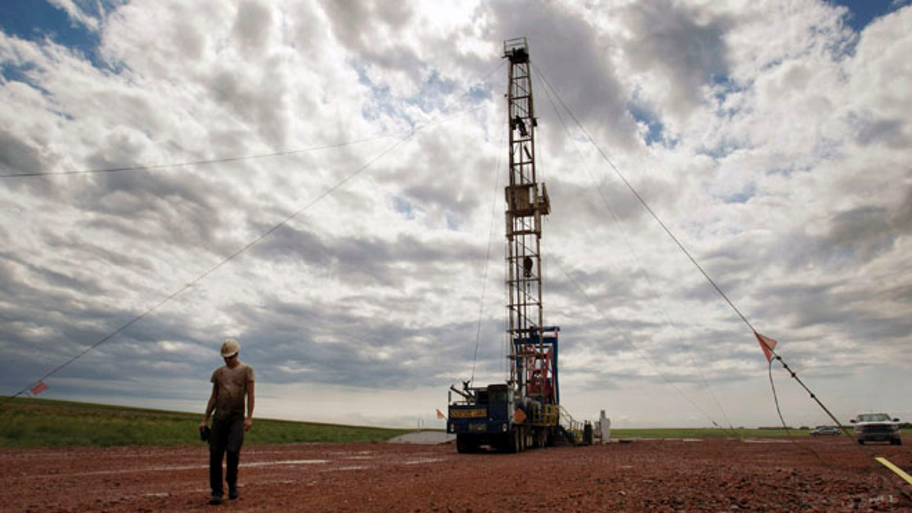 July 26, 2011: A worker walks by an oil derrick outside of Williston, N.D. Relief could be on the horizon for strapped public services in the Northern Plains' booming oil patch, as elected leaders in Montana and North Dakota move to steer more money into the region during the states' upcoming legislative sessions.
