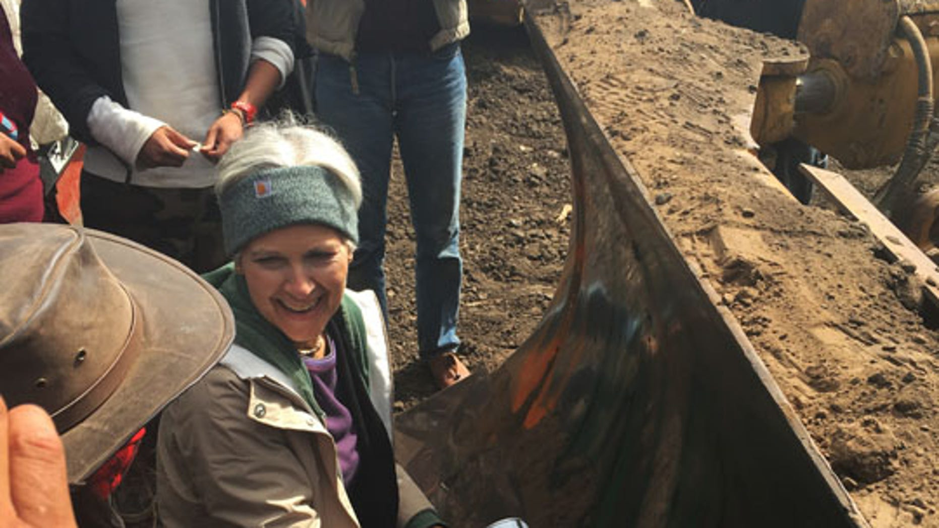 """Sept. 6, 2016: Green Party presidential candidate Jill Stein prepares to spray-paint """"I approve this message"""" in red paint on the blade of a bulldozer at a protest against the Dakota Access Pipeline in the area of Morton County, N.D."""